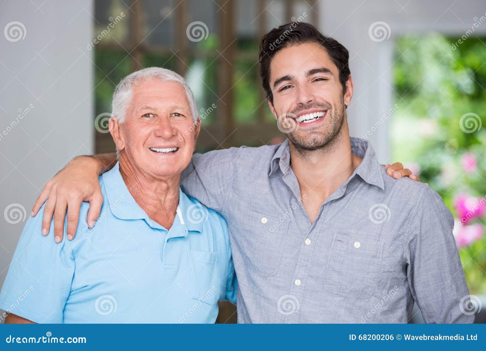 Porträt des lächelnden Vaters und des Sohns mit dem Arm herum