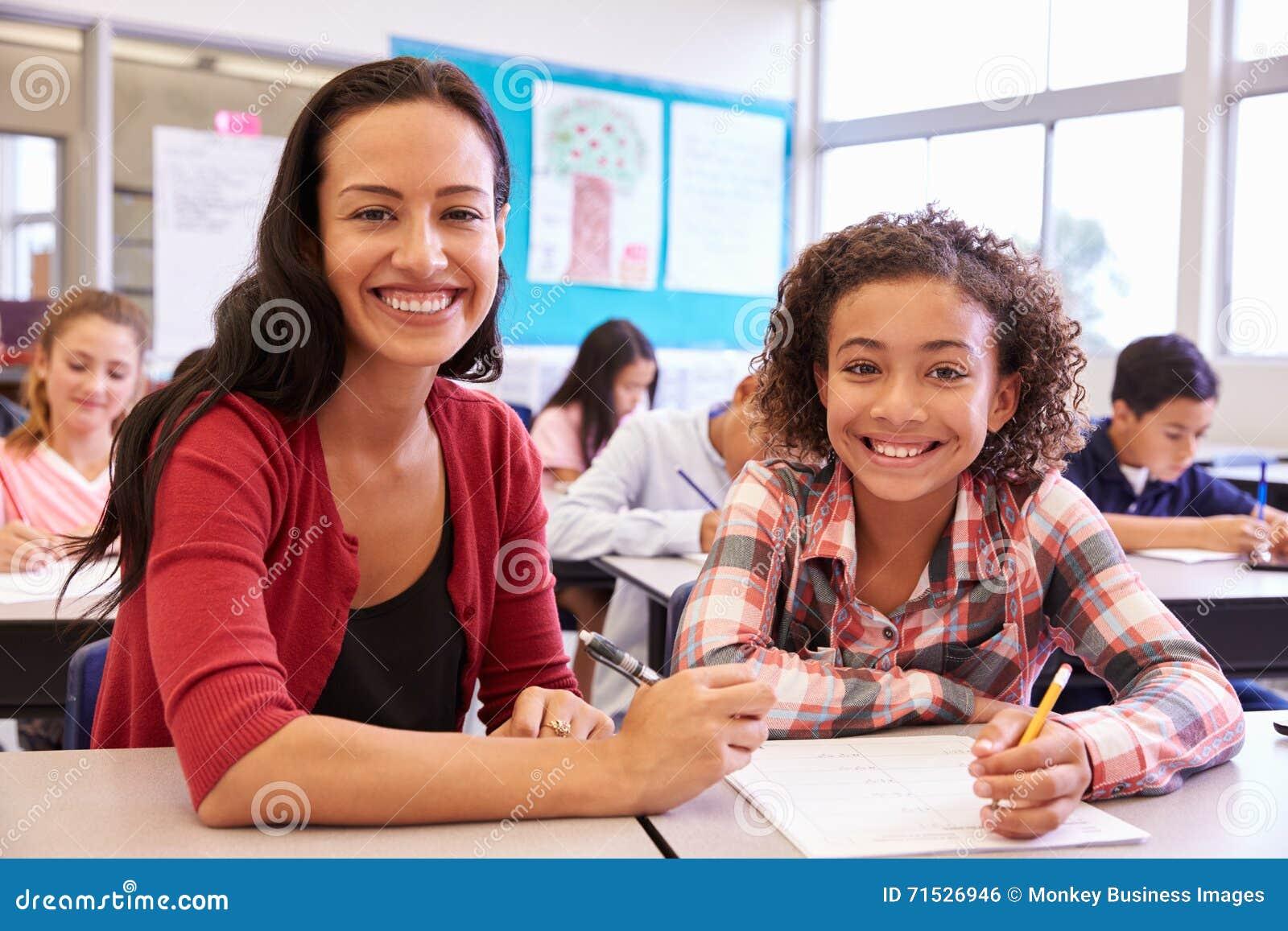 Porträt des Lehrers mit Volksschulemädchen an ihrem Schreibtisch