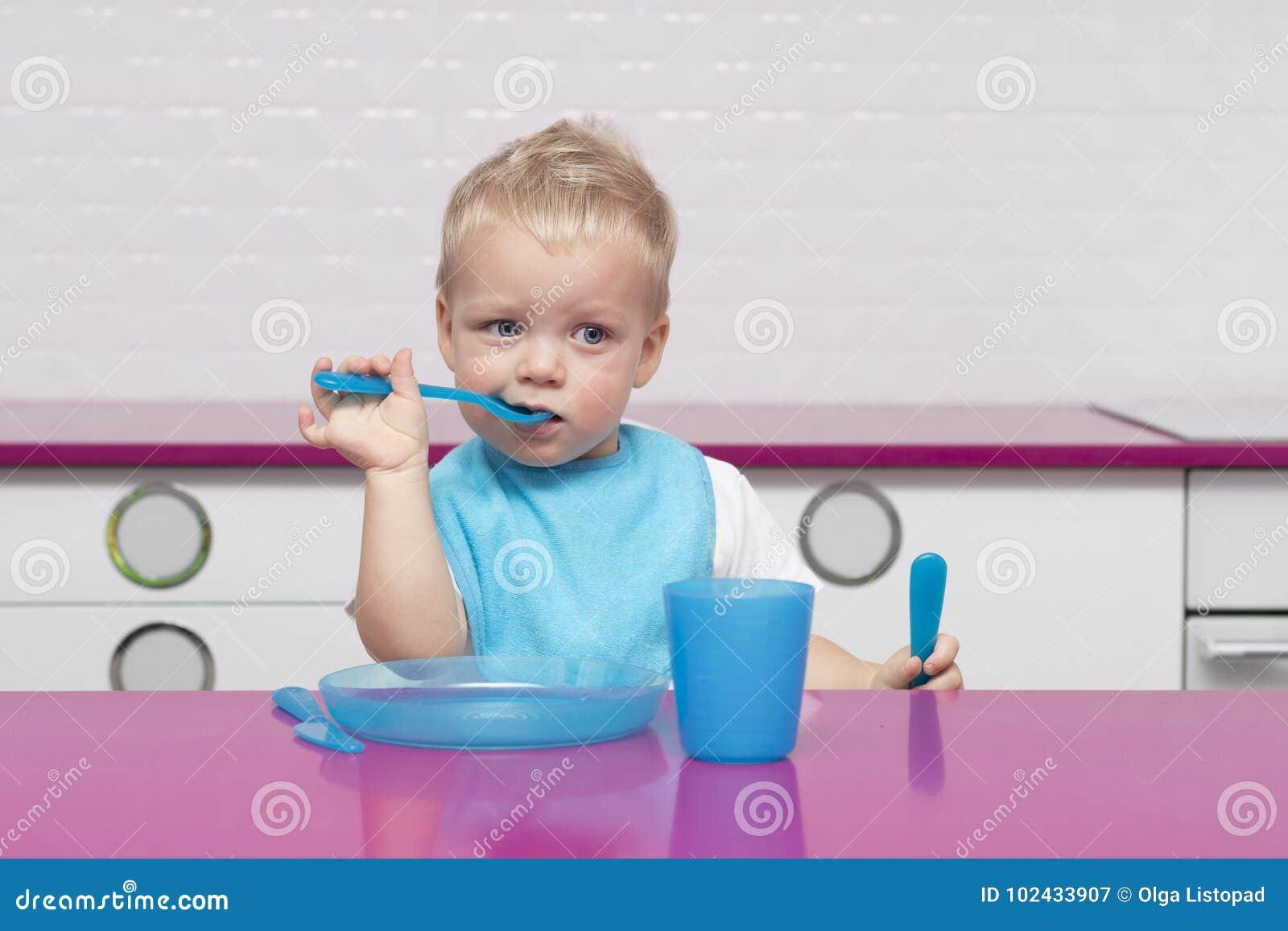 Porträt des lustigen jungen Babys in einem blauen Schellfisch mit Gabel und im Messer in seinen Händen im Hochstuhl in der modern