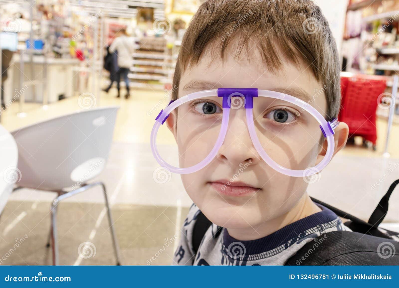Porträt des lustigen netten Jungen, der die merkwürdigen Gläser gemacht von den Leuchtstoffneonröhren, Einkaufszentrum trägt