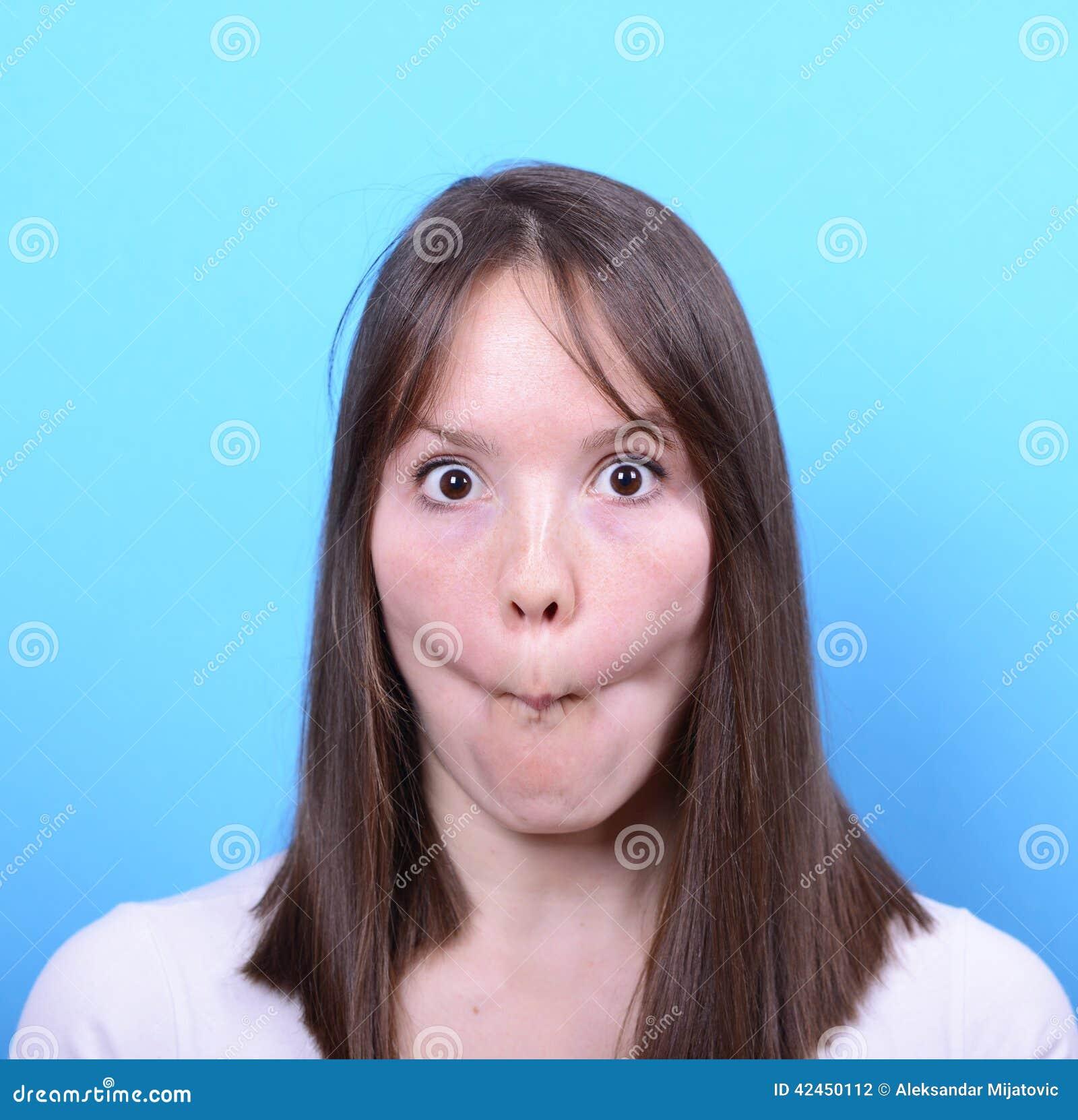 Porträt des Mädchens mit lustigem Gesicht gegen blauen Hintergrund
