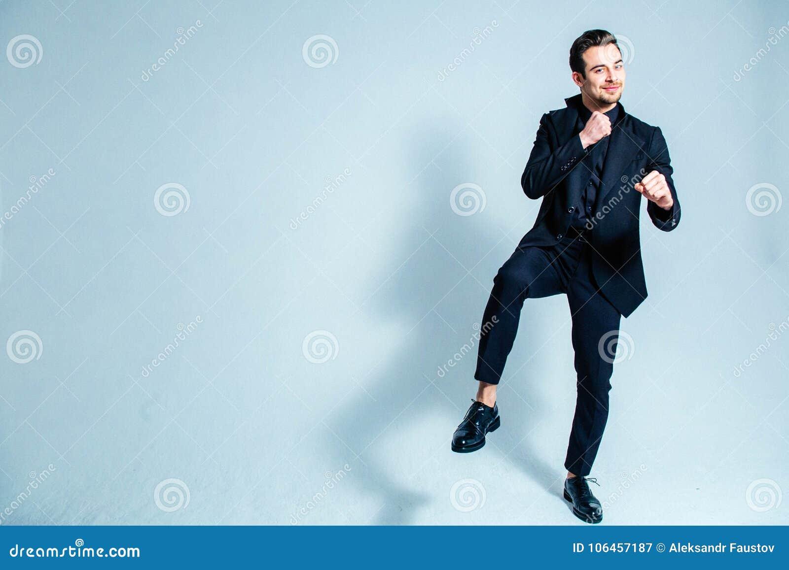 Porträt des Mannes in einem schwarzen Anzug in einer kämpfenden Position, Händchenhalten nahe seinem Kasten, lächelnd und schauen
