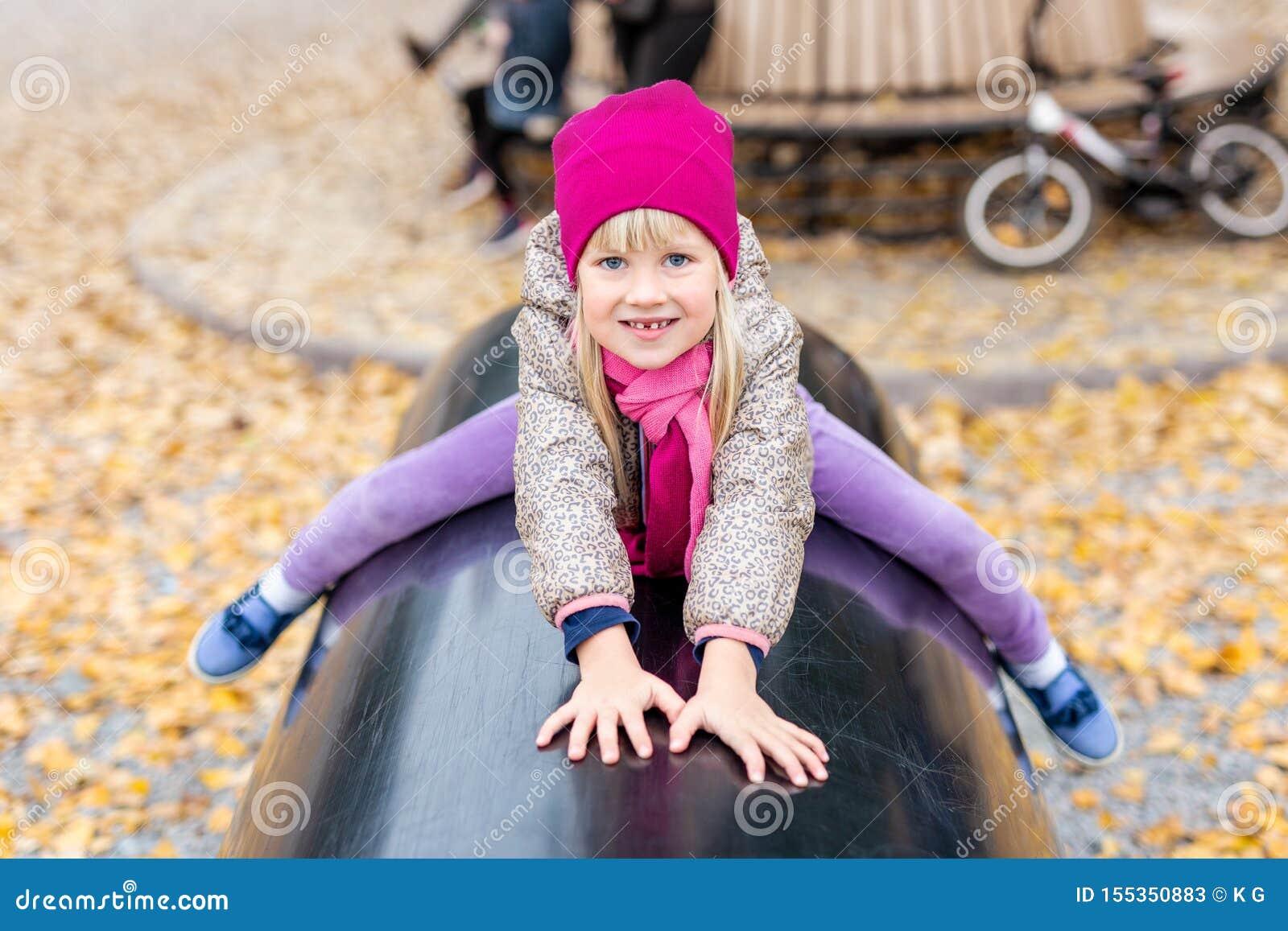 Porträt des netten kaukasischen blonden kleinen Mädchens, das den Spaß spielt am modernen Spielplatz im Freien am Stadtpark im He