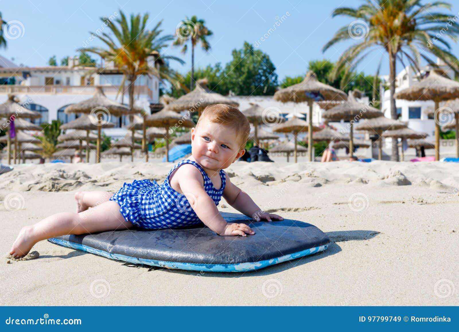 Porträt des netten kleinen Babys in der Schwimmenklage auf Strand im Sommer