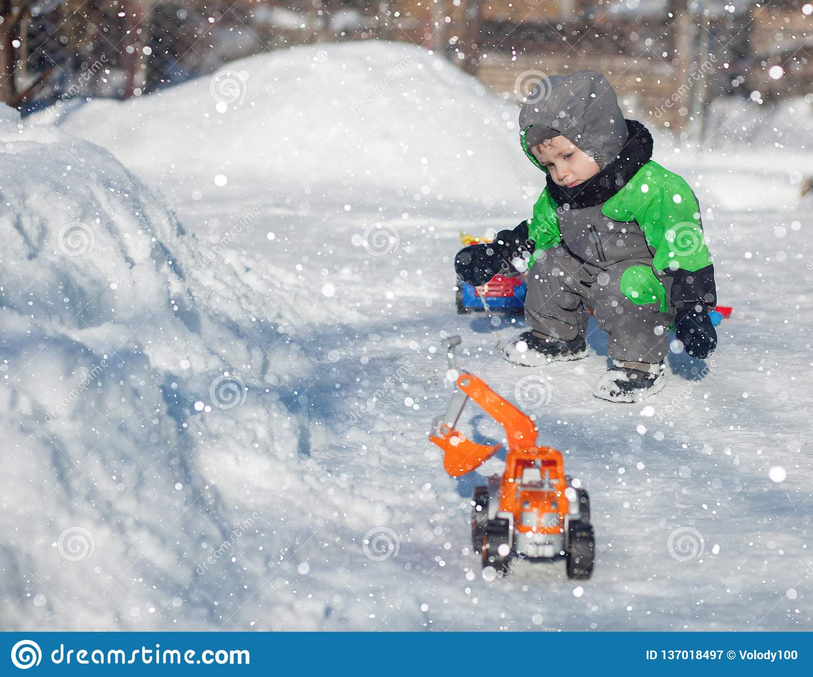 Porträt des netten kleinen Kleinkindes, das auf Schnee sitzt und mit seinem gelben Traktorspielzeug im Park spielt Little Boy-Ste