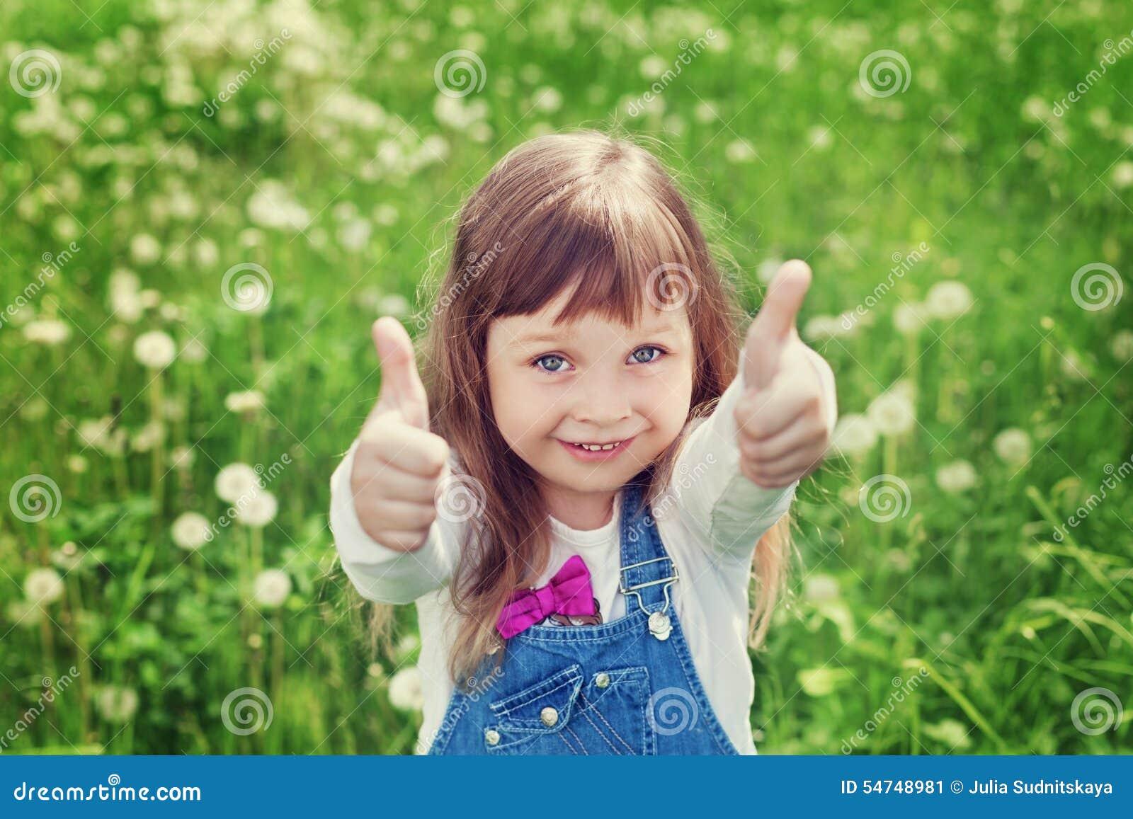 Porträt des netten kleinen Mädchens mit den Daumen zeigt sich eine Klasse auf der Blumenwiese, glückliches Kindheitskonzept, das