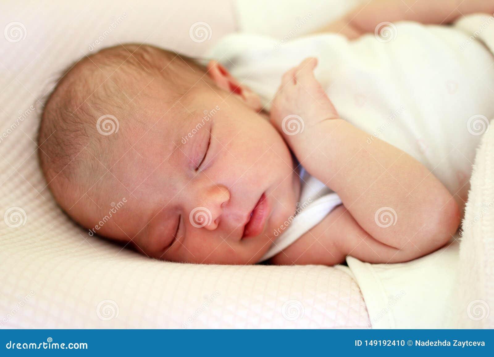 Portr?t des netten neugeborenen Babys, das auf einem rosa Bett unter beige Decke schl?ft