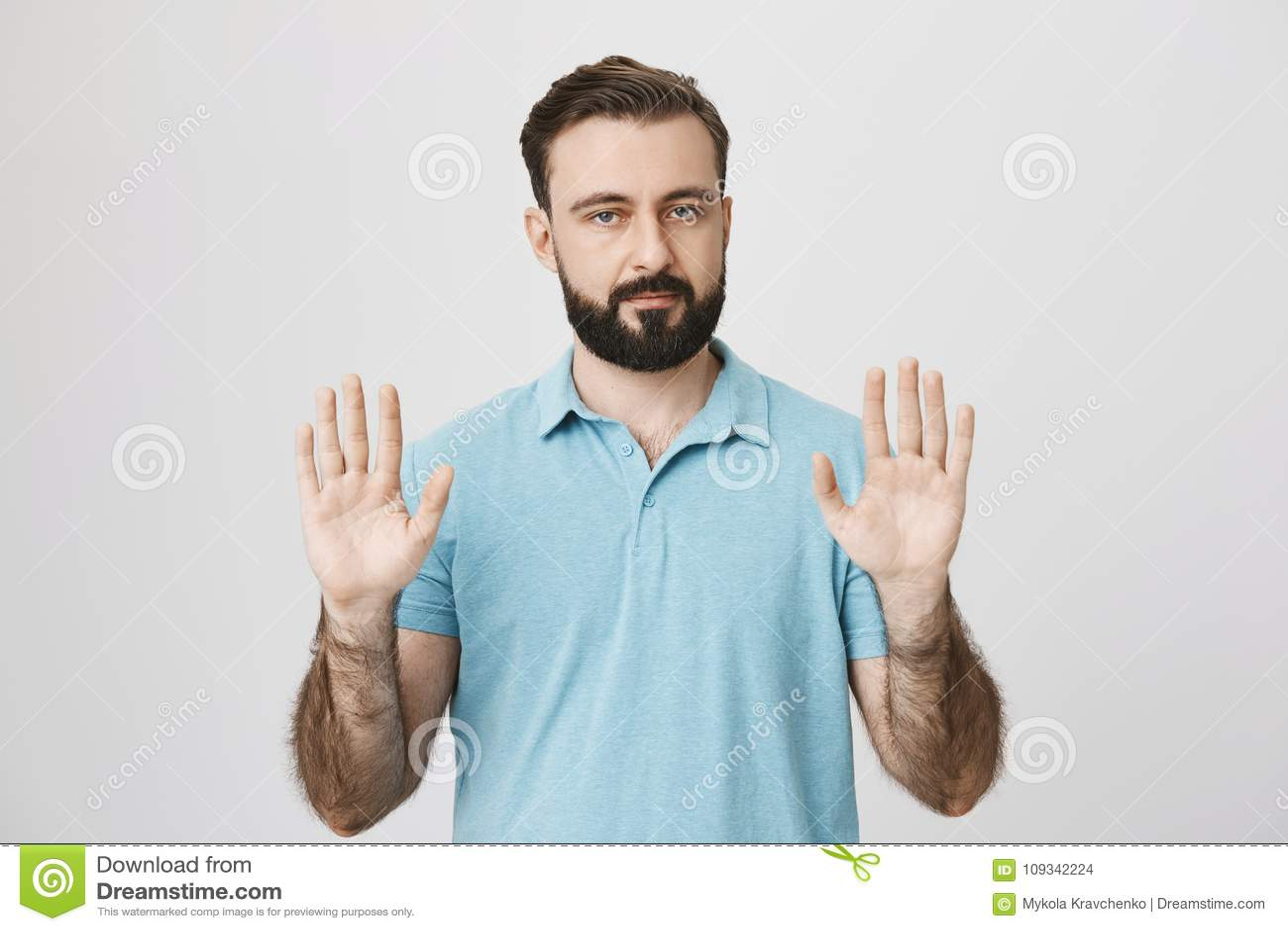 Porträt des ruhigen erwachsenen Mannes mit dem Bart, der seine Palmen anhebt und Kamera, stehend über grauem Hintergrund betracht