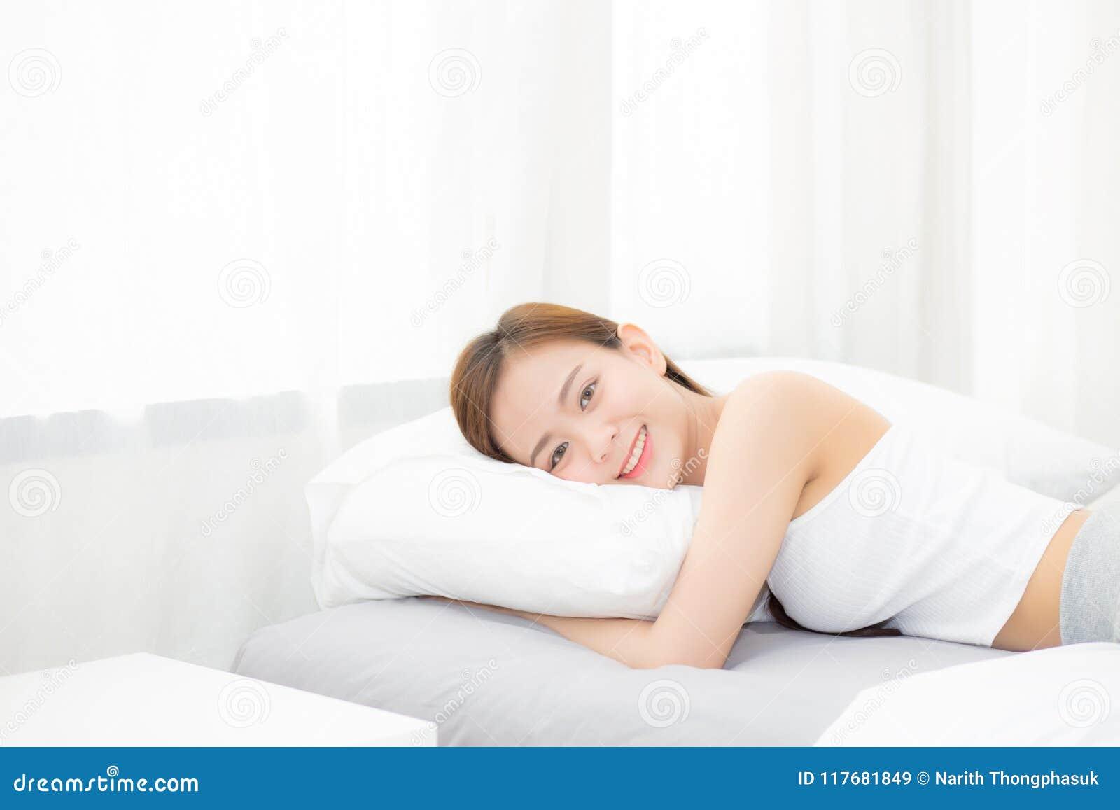 Porträt des schönen asiatischen Schlafes der jungen Frau, der im Bett mit Kopf auf dem Kissen bequem und glücklich liegt