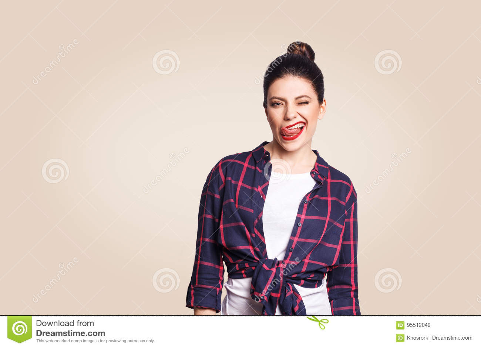 Porträt des schönen glücklichen Mädchens in der zufälligen Art, die Kamera mit lustigem Gesicht und Zunge heraus und Wink betrach