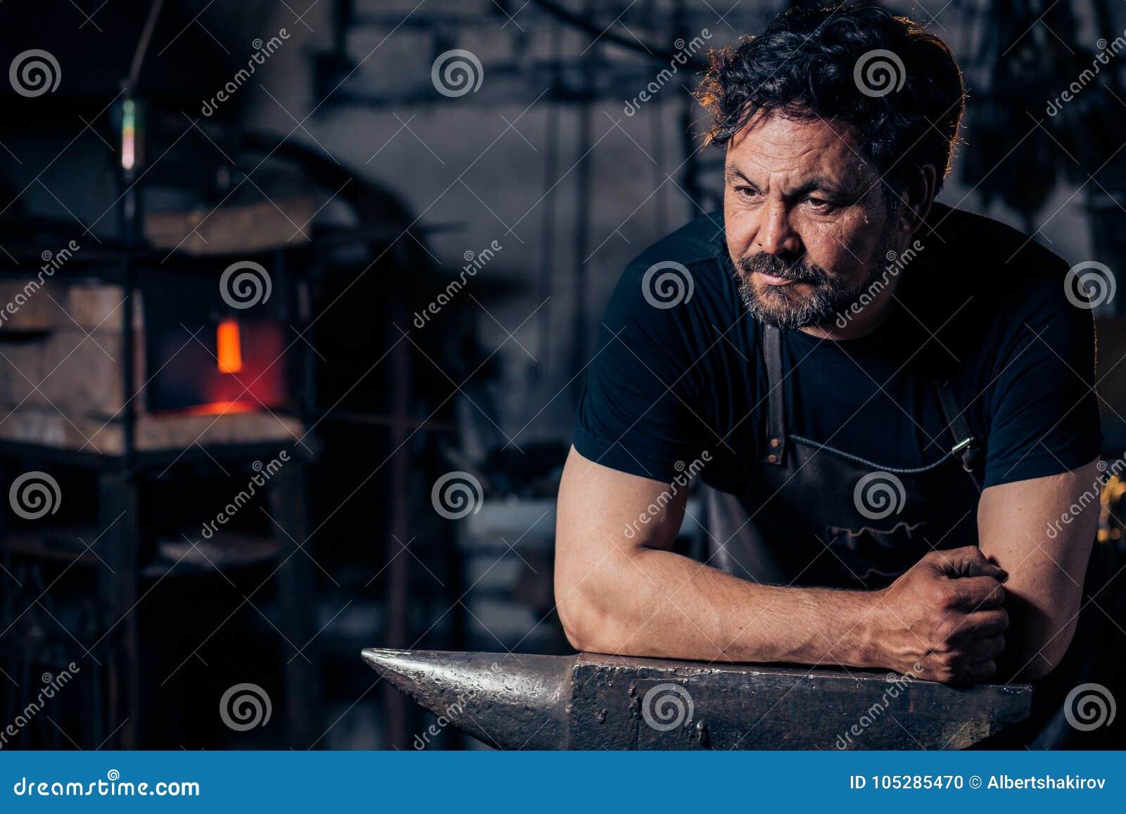 Porträt des Schmiedes vorbereitend, Metall auf dem Ambosse zu bearbeiten