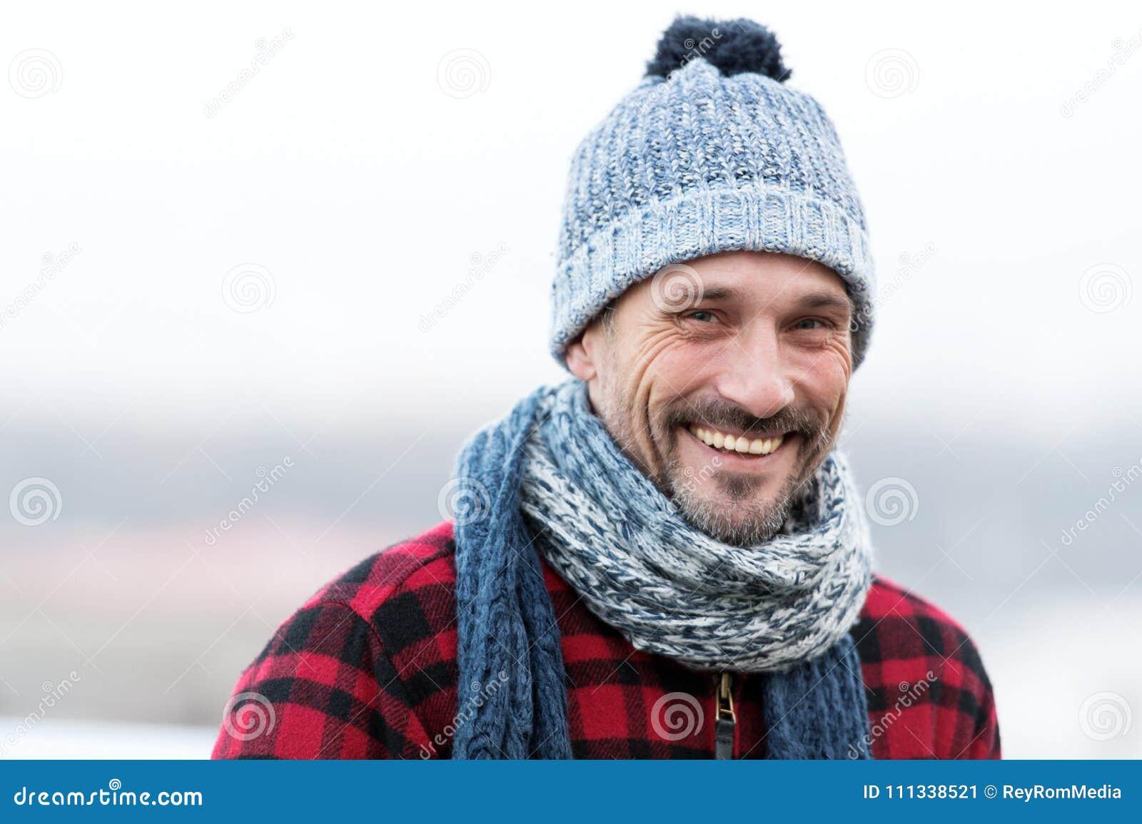 Porträt des städtischen sehr lächelnden Kerls Glücklicher Mann im Hut mit Ball und Schal Lustiger Mann lächelt zu Ihnen Nahaufnah