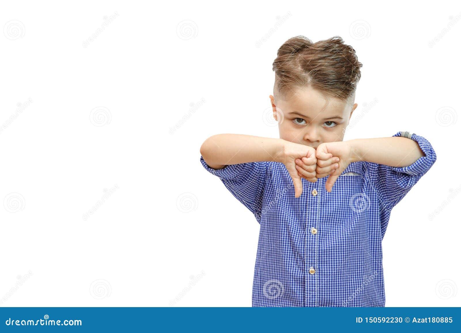 Porträt des stilvollen hübschen Jungen lokalisiert auf weißem Hintergrund Junge, der unten Daumen zeigt