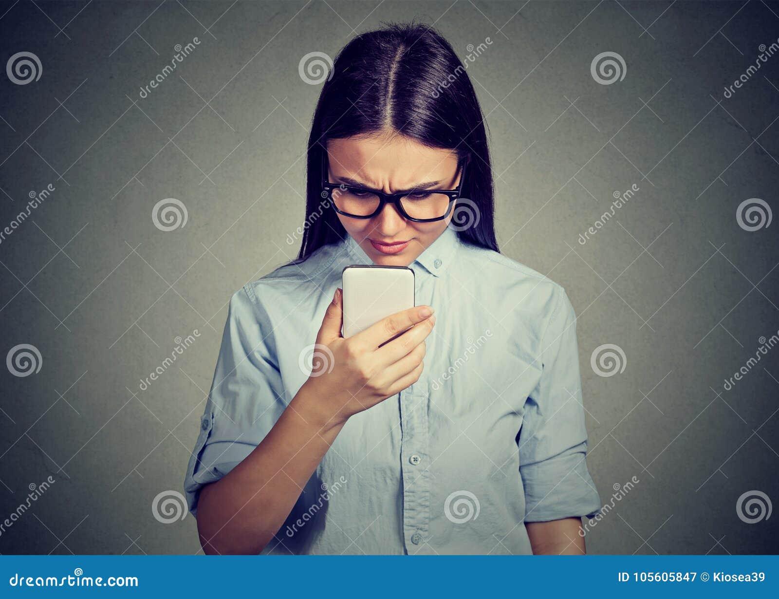 Porträt des Unterhaltungsc$simsens der traurigen ernsten Frau des Umkippens an einem Telefon missfiel mit Gespräch