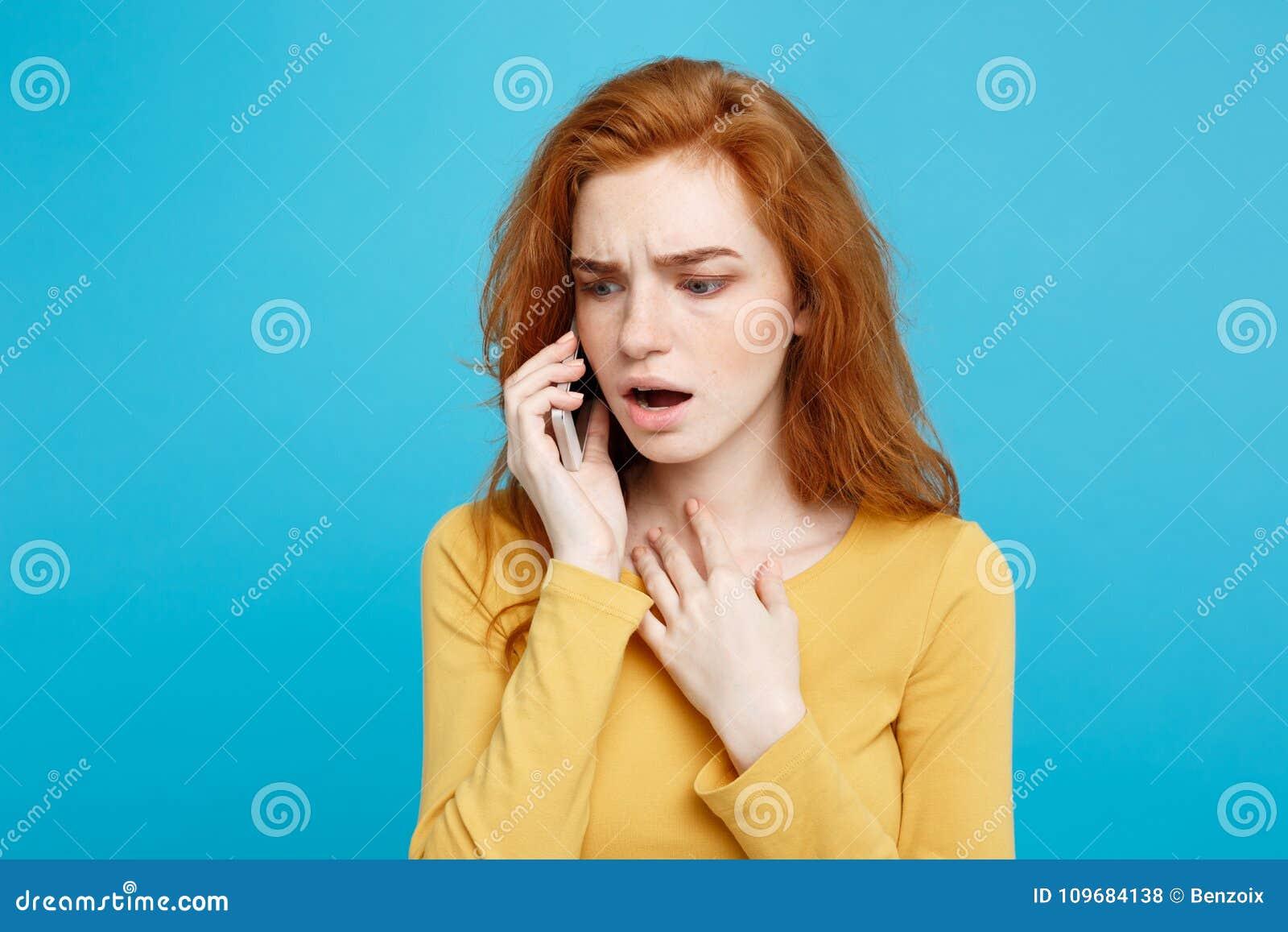Porträt einer überraschten verwirrten Frau im gelben zufälligen nennenden Handy lokalisiert über blauem Hintergrund