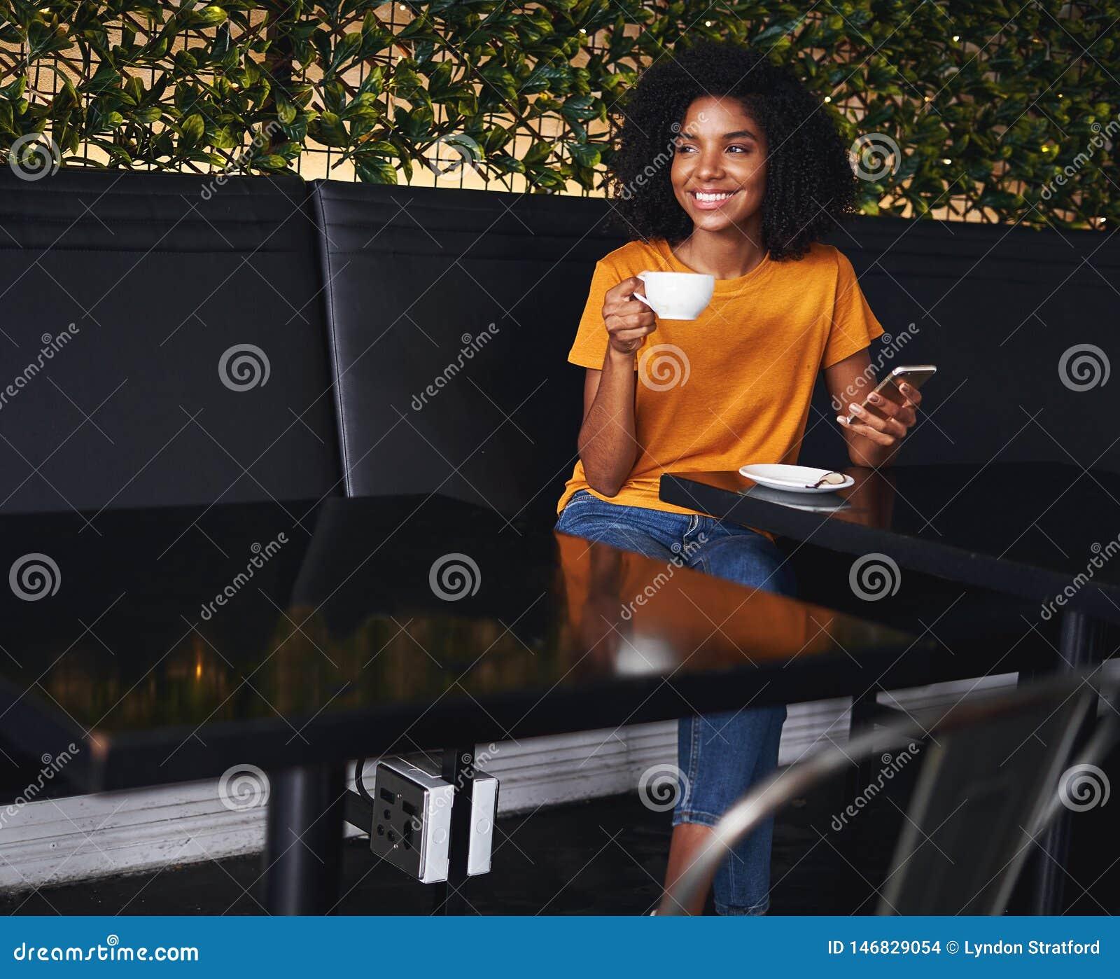 Porträt einer afrikanischen jungen Frau, die im Café sitzt