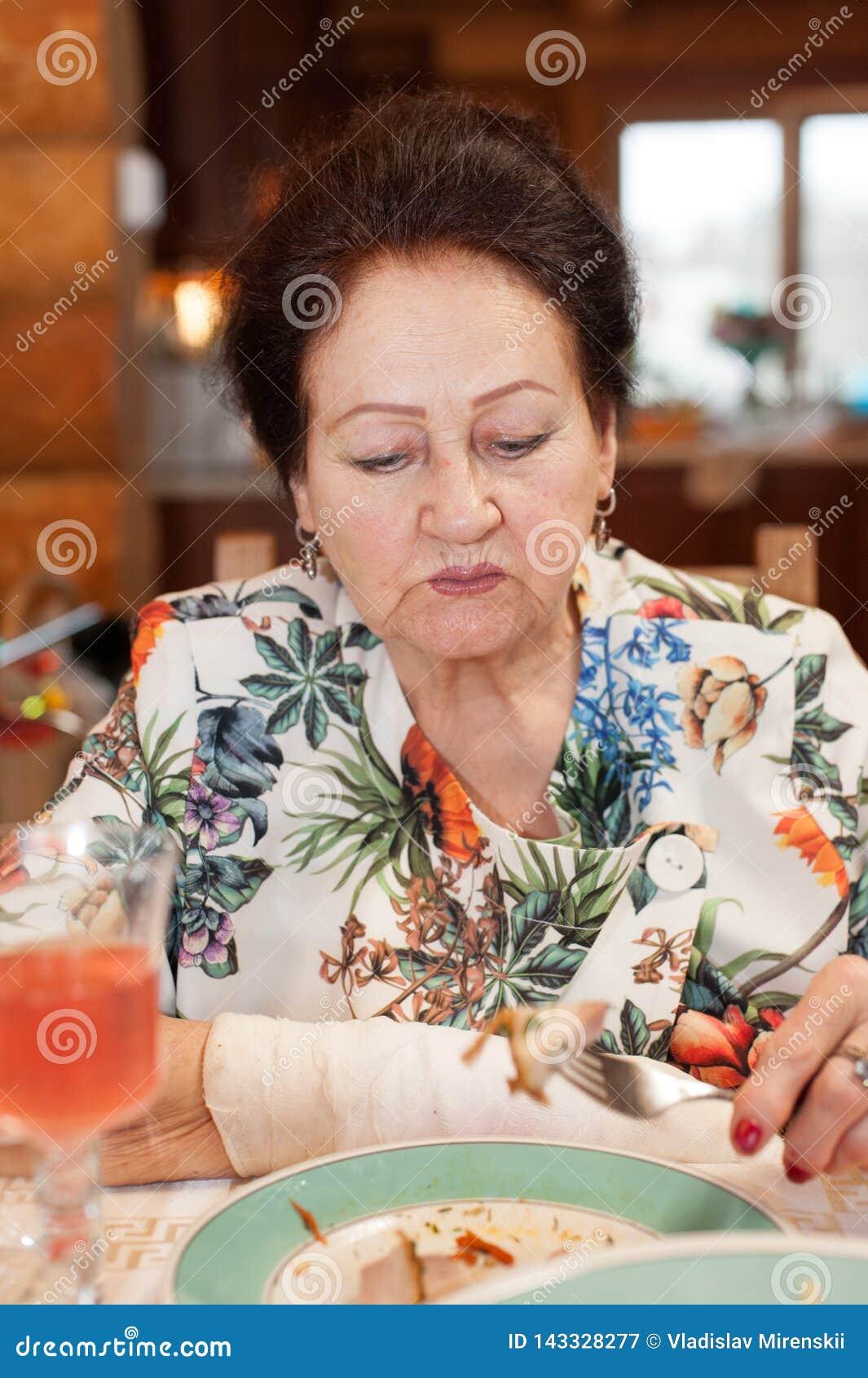 Porträt einer eleganten älteren Dame mit einer verbundenen Hand