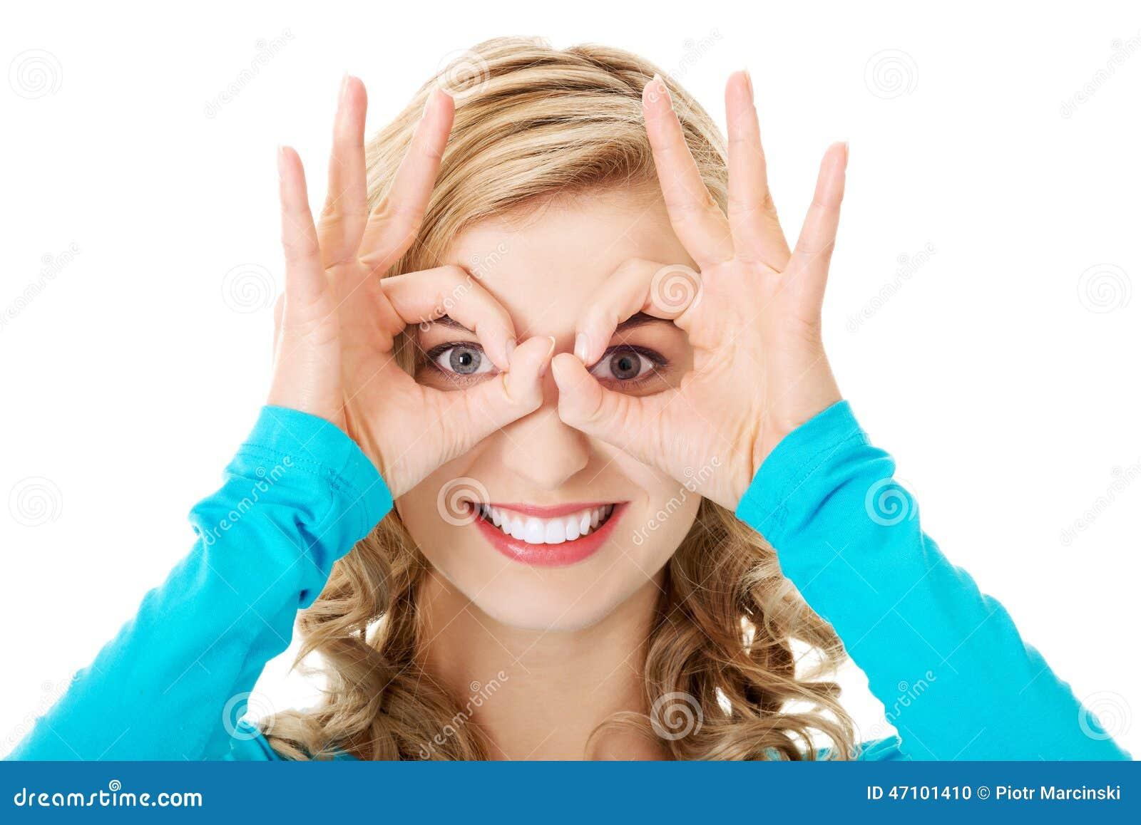 Porträt einer Frau, die okayzeichen auf Augen zeigt