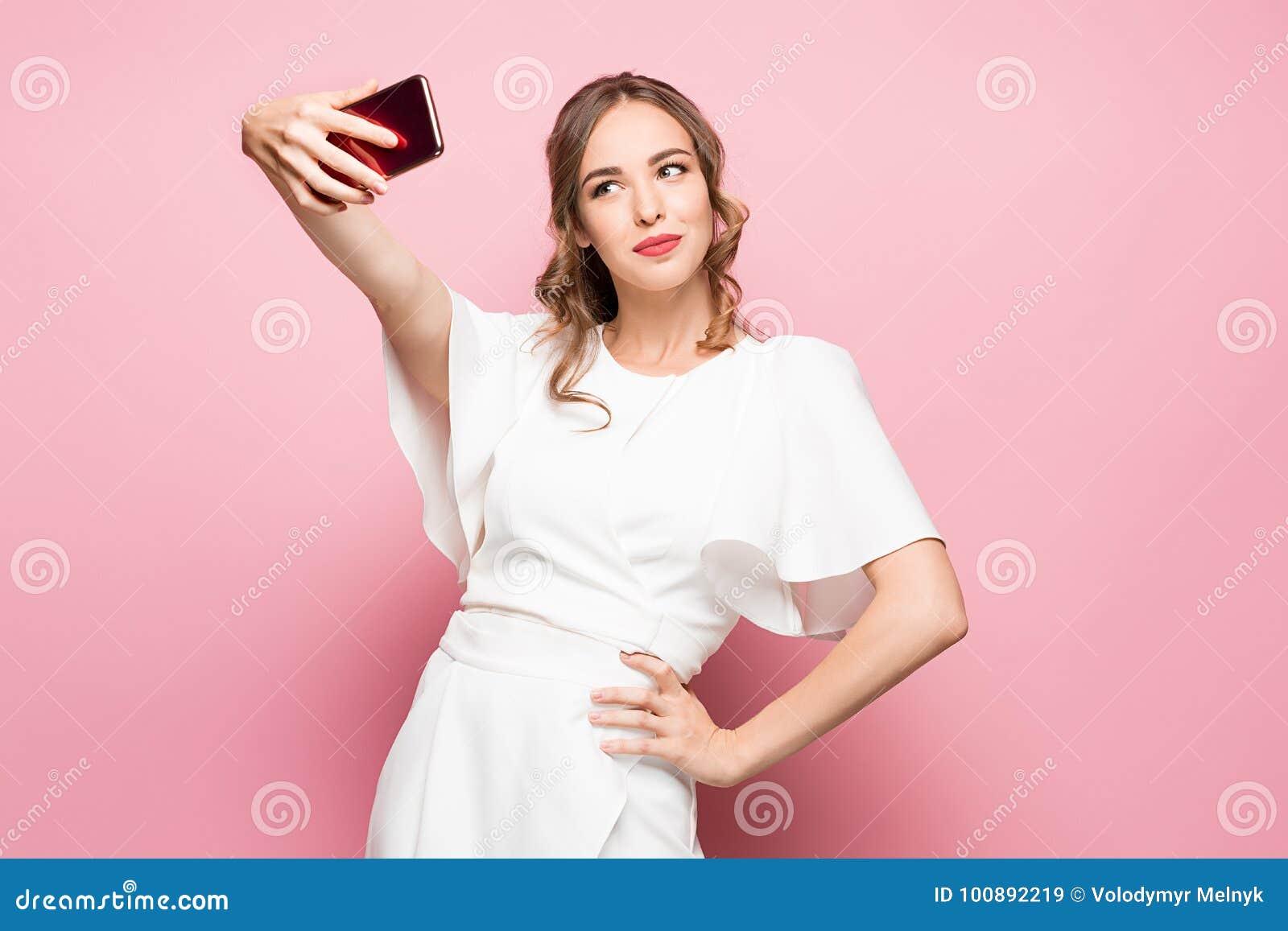 Porträt einer jungen attraktiven Frau, die selfie Foto mit Smartphone auf einem rosa Hintergrund macht