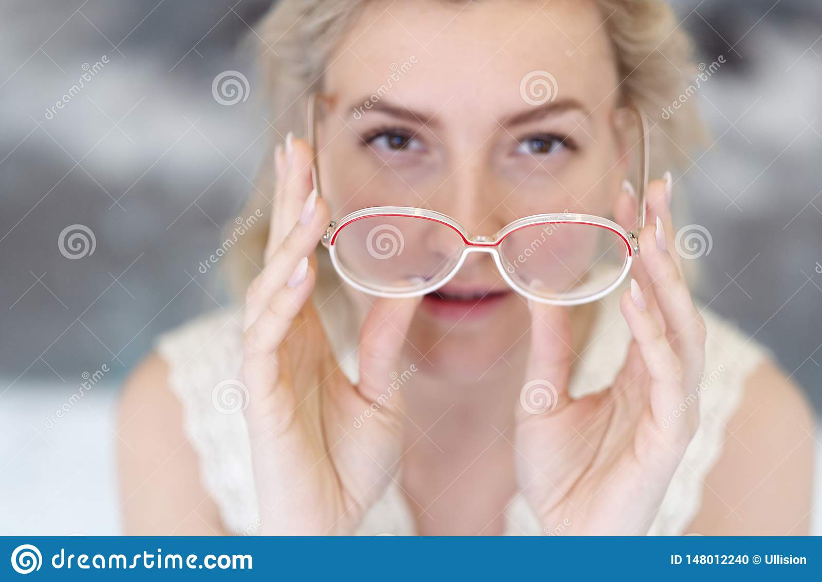 Porträt einer jungen Frau mit den Gläsern und blondem Haar, welche die Gläser vor ihrem Gesicht, ihr Gesicht unscharf halten