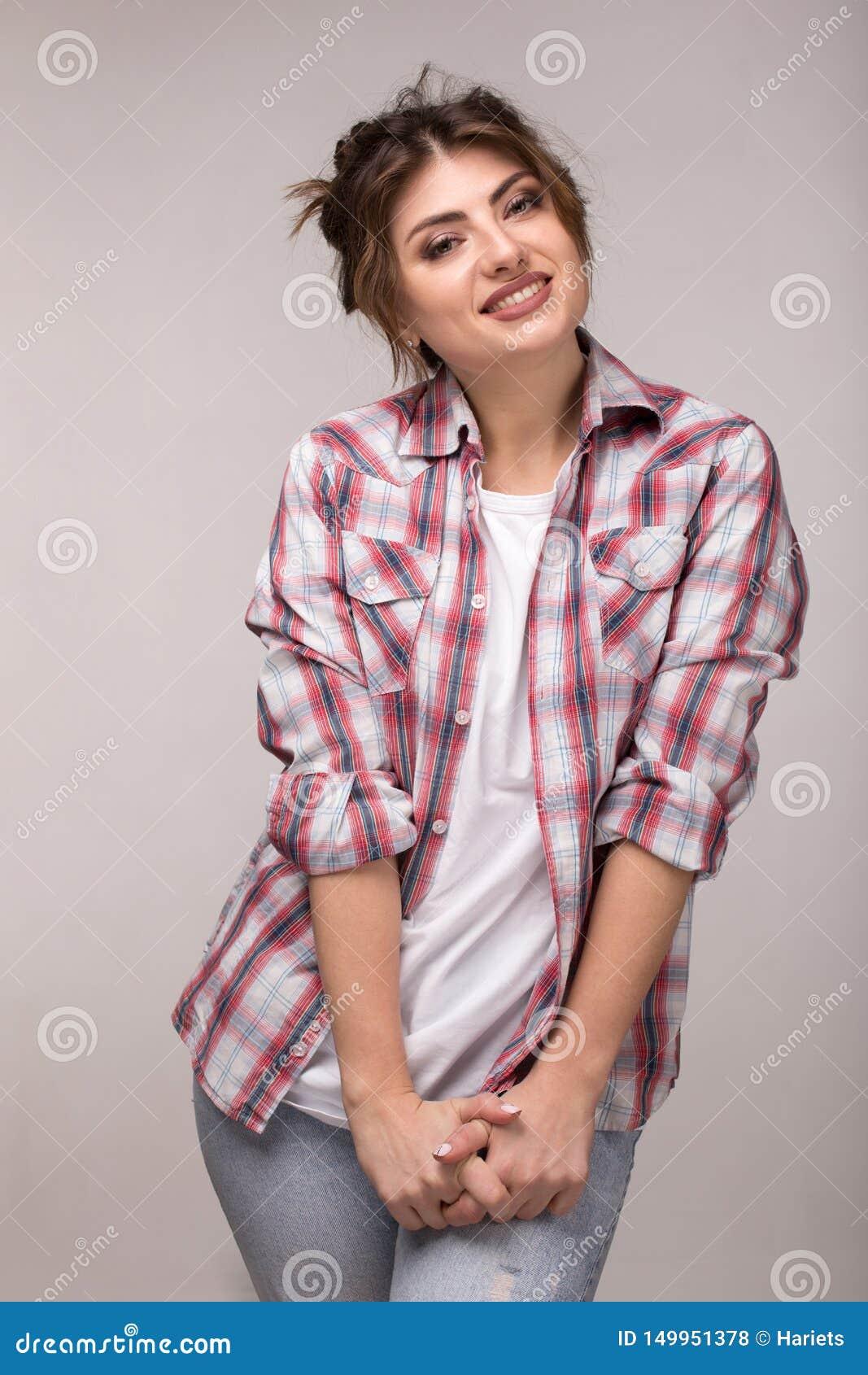Porträt einer jungen lächelnden Frau im karierten Hemd und im weißen T-Shirt, stehend über grauer Wand