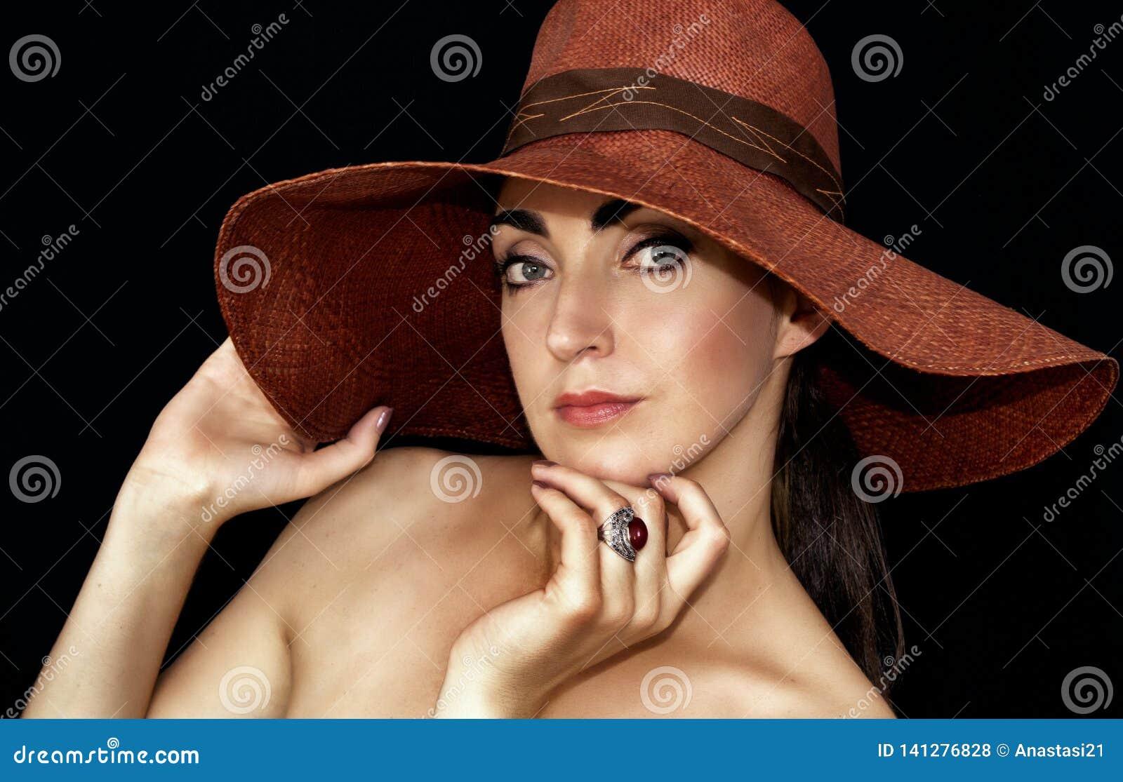 Porträt einer schönen jungen Frau in einem Hut auf einem schwarzen Hintergrund