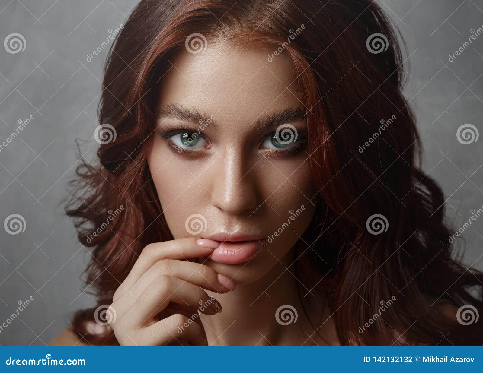 Porträt einer schönen jungen Frau mit dem Fliegenhaar Nettes Mädchen, das auf einem grauen Hintergrund aufwirft Große schöne Auge