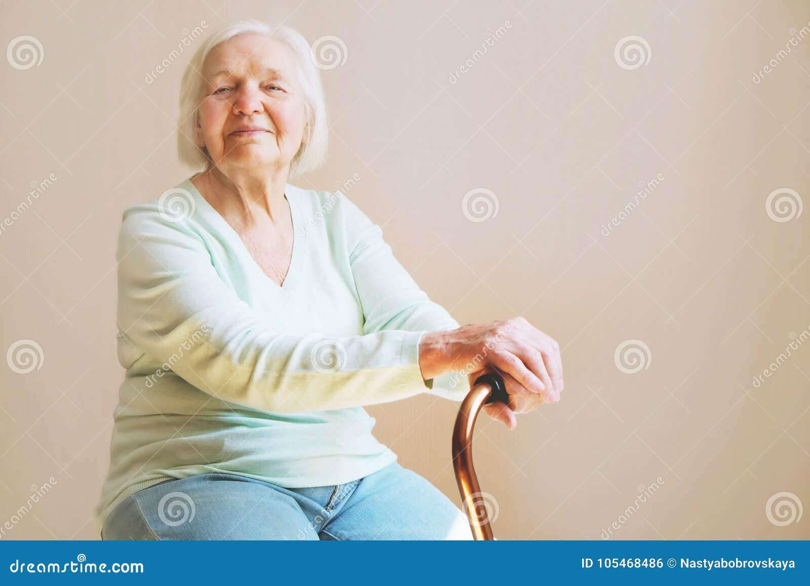 Porträt einer schönen lächelnden älteren Frau mit gehendem Stock auf hellem Hintergrund zu Hause