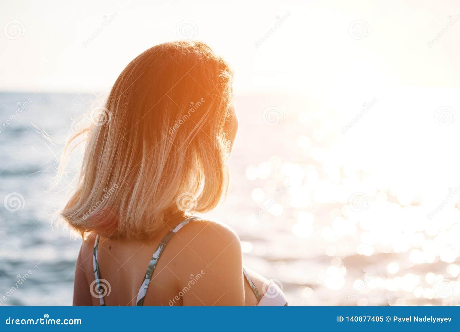 Porträt einer schönen lächelnden jungen Frau im Bikini auf dem Strand Weibliches Modell, das im Badeanzug auf Seeufer aufwirft Gl