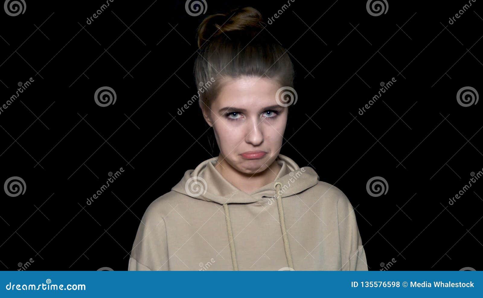 Porträt einer sehr traurigen und deprimierten jungen Frau lokalisiert auf schwarzem Hintergrund Sehr traurige, unglückliche Frau