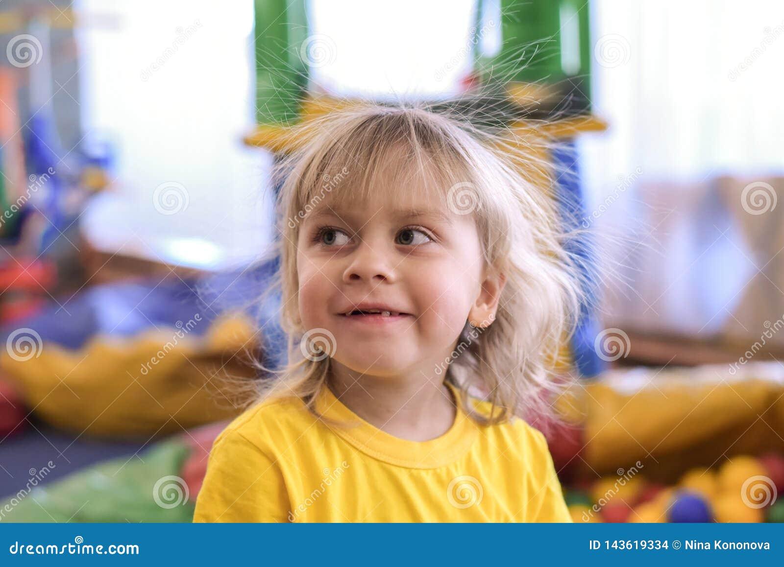 Porträt eines blonden Jungen in einem gelben T-Shirt Das Kinderlächeln und -spiele im Spielzimmer der Kinder