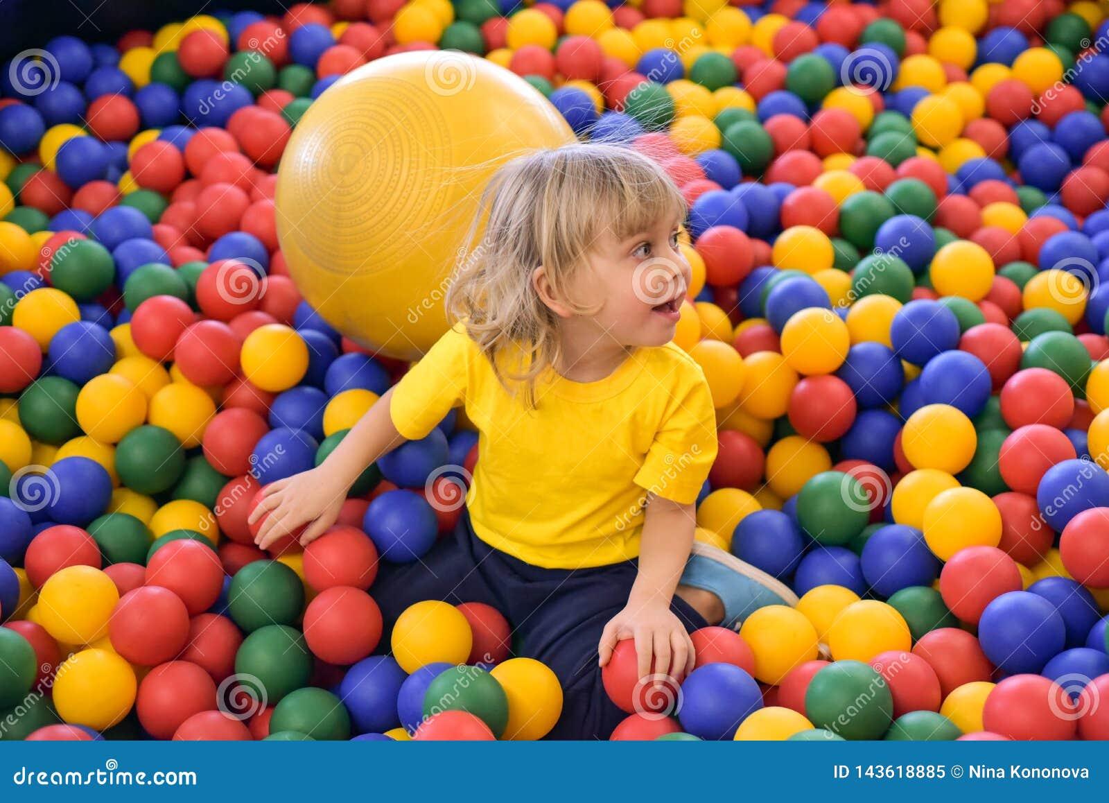 Porträt eines blonden Jungen in einem gelben T-Shirt Das Kinderlächeln und -spiele im Spielzimmer der Kinder Ballpool