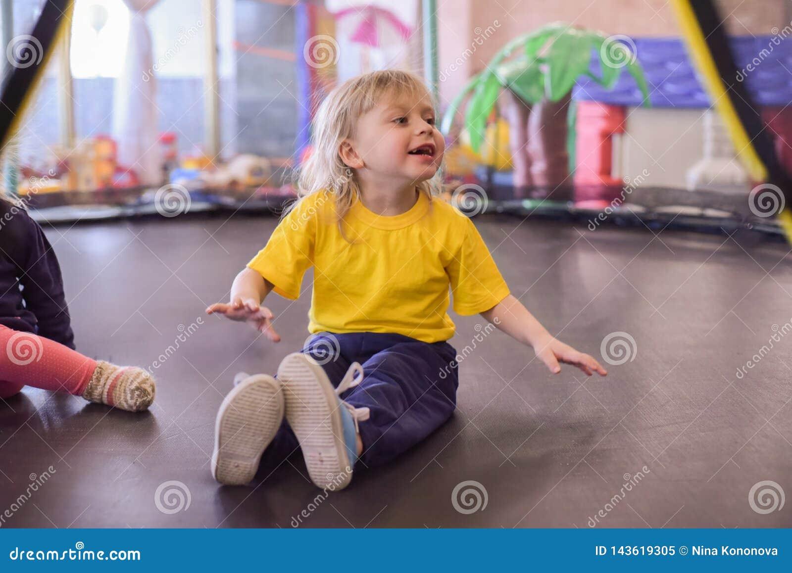 Porträt eines blonden Jungen in einem gelben T-Shirt Das Kinderlächeln und -spiele im Spielzimmer der Kinder Das Kind springt auf