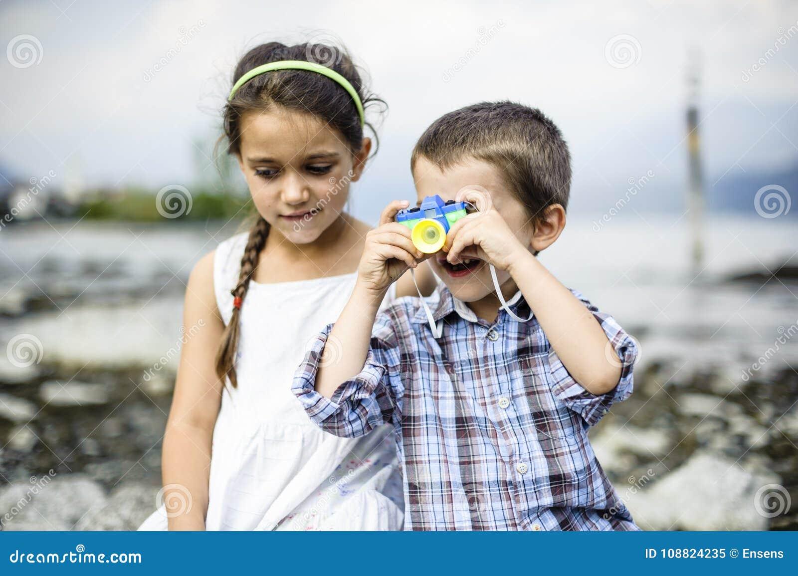 Porträt eines Bruders und der Schwesterkinder mit Spielzeugkamera