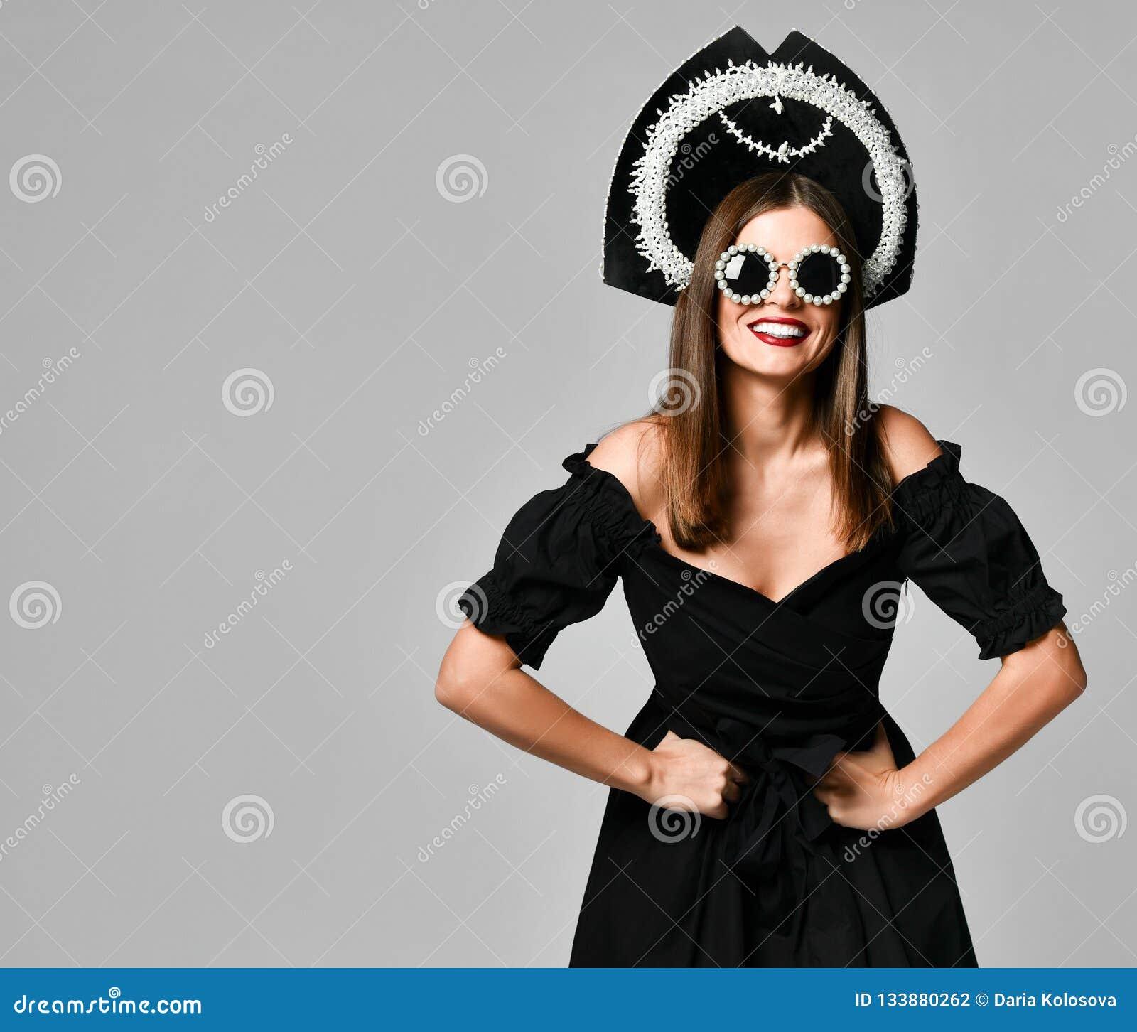 Porträt eines eleganten brunette schwarzen Kleides, der schwarzen Sonnenbrille, der kokoshnik Kappe, des langen Haares und des sc