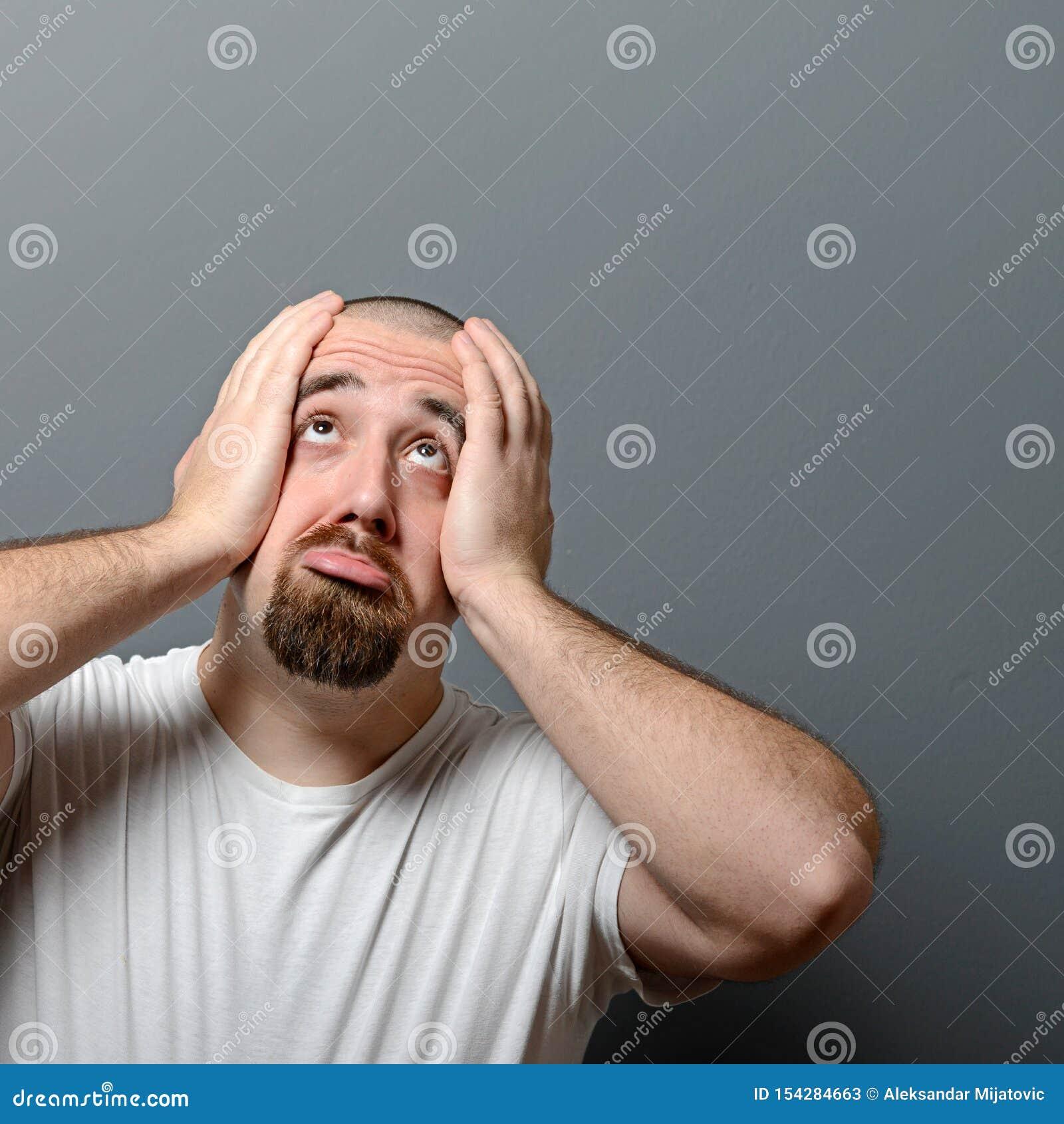 Porträt eines hoffnungslosen Mannes im Schock gegen grauen Hintergrund