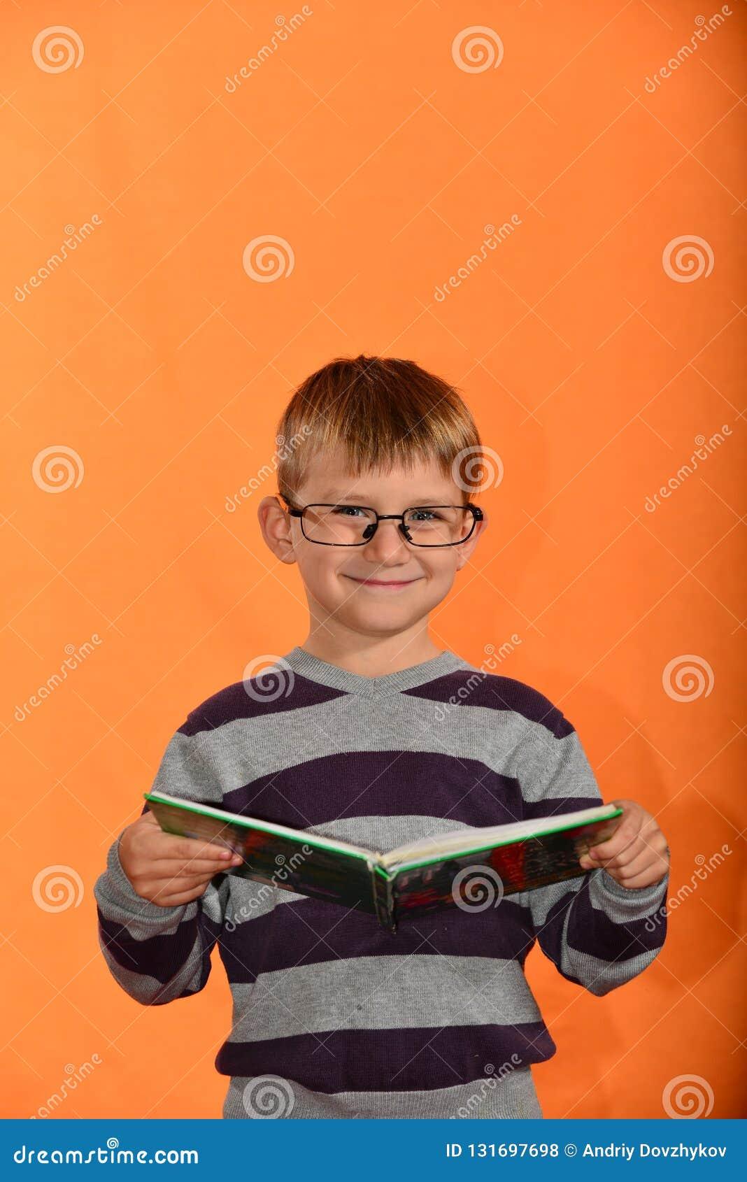 Porträt eines Jungen in den Gläsern mit einem Buch in seinen Händen, ein netter Schüler auf einem gelben Hintergrund