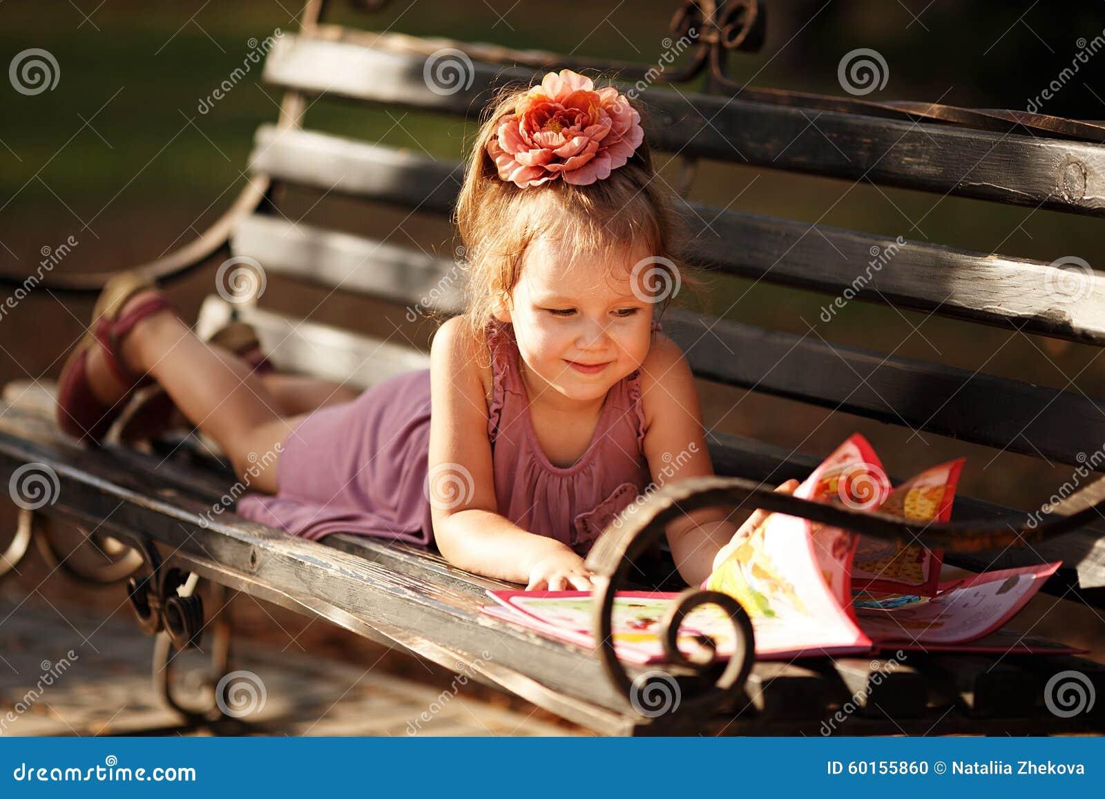 Porträt eines kleinen Mädchens, das ein Buch der Kinder liegt auf einem p liest