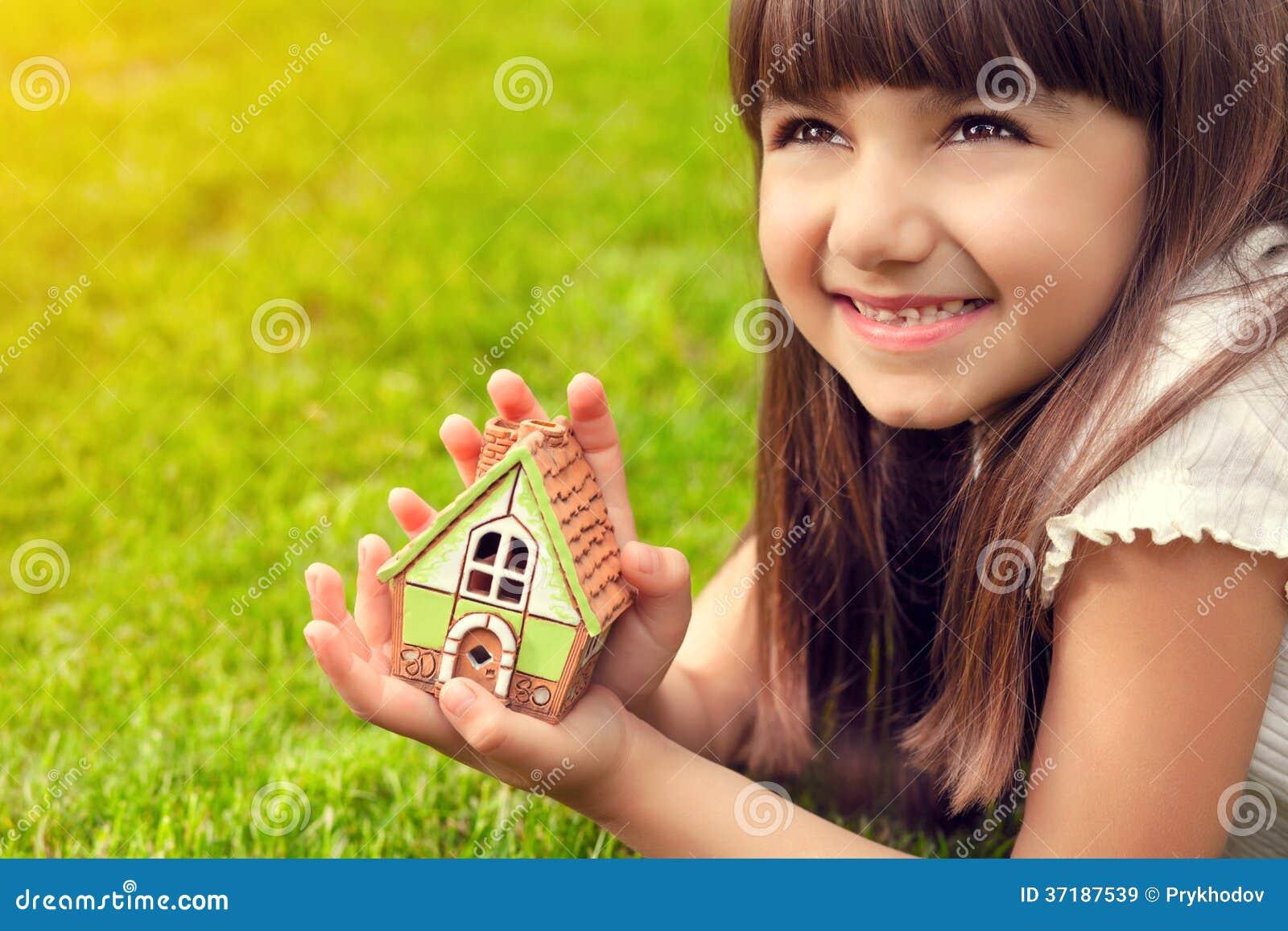 Porträt eines kleinen Mädchens mit Haus in der Hand auf einem Hintergrund von
