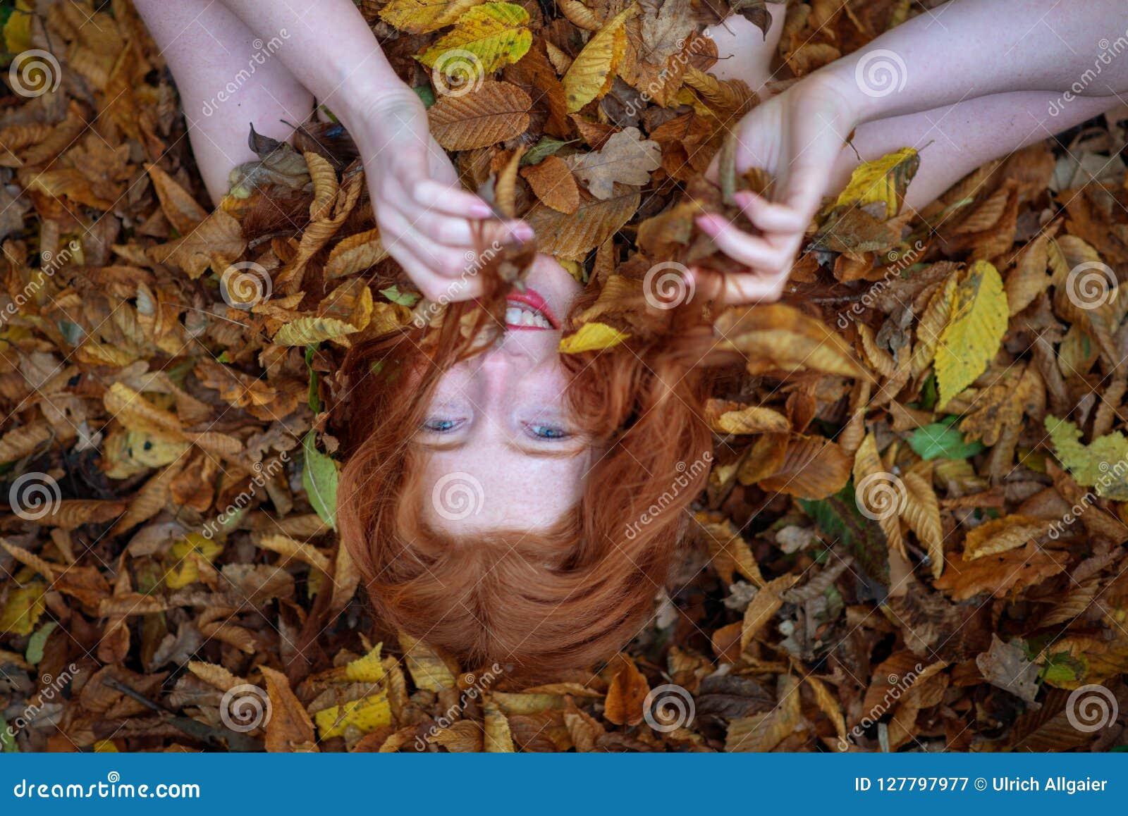 Porträt eines netten jungen reizenden Mädchens, bedeckt mit den roten und orange herbstlichen Blättern Schöne sexy Frau, die auf