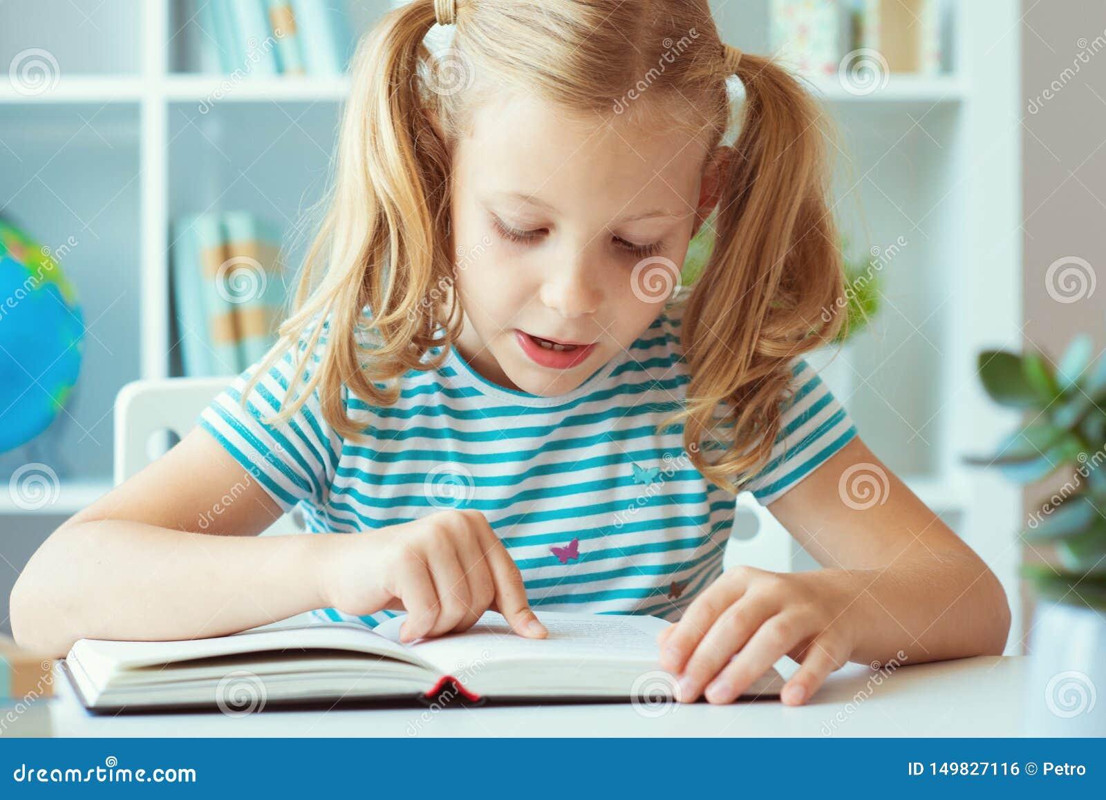 Porträt eines netten kleinen Mädchens las Buch am Tisch im Klassenzimmer