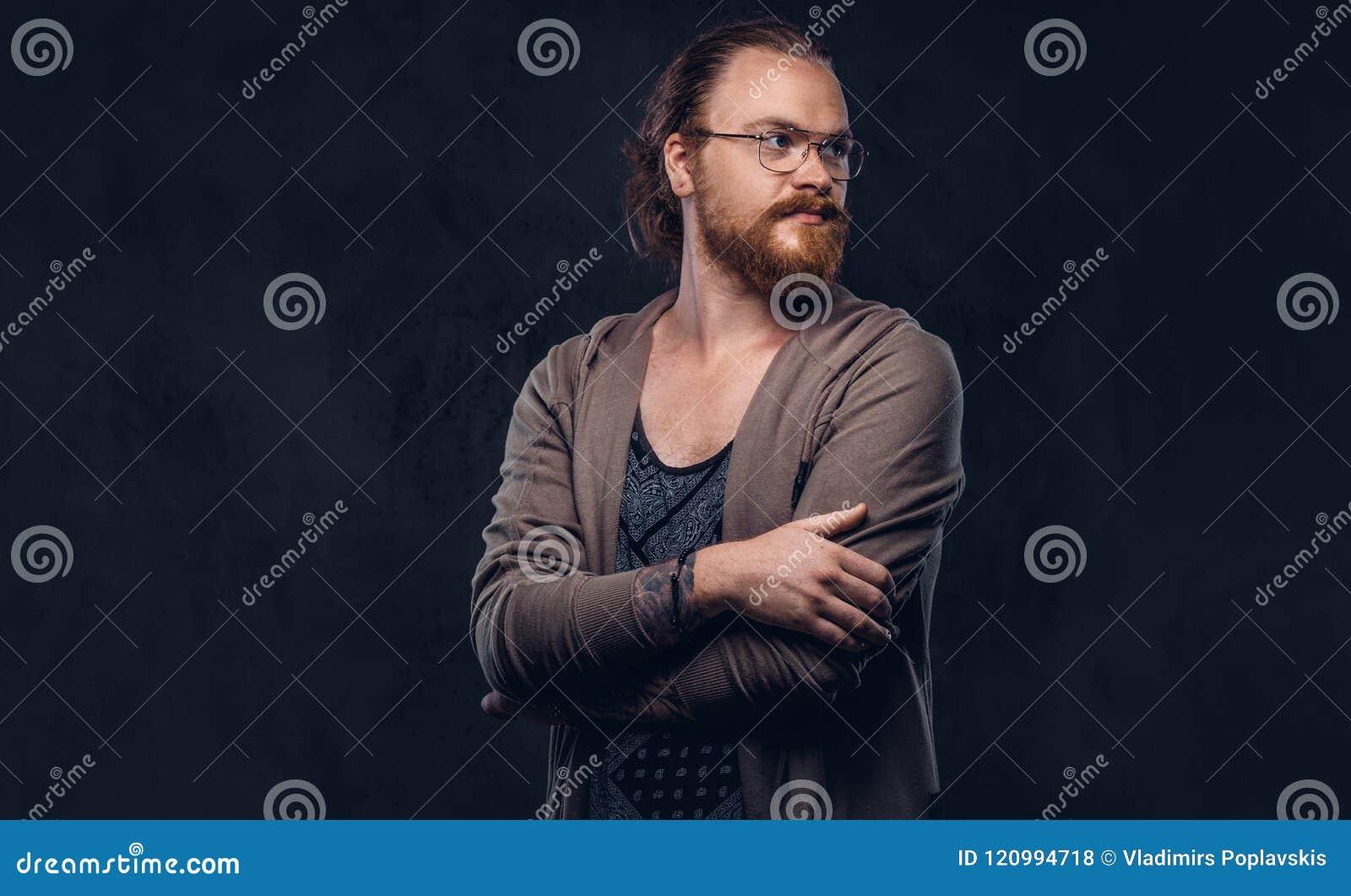 Porträt eines Rothaarigehippie-Mannes kleidete in der zufälligen Kleidung mit den Gläsern und Vollbart an und stand mit den gekre
