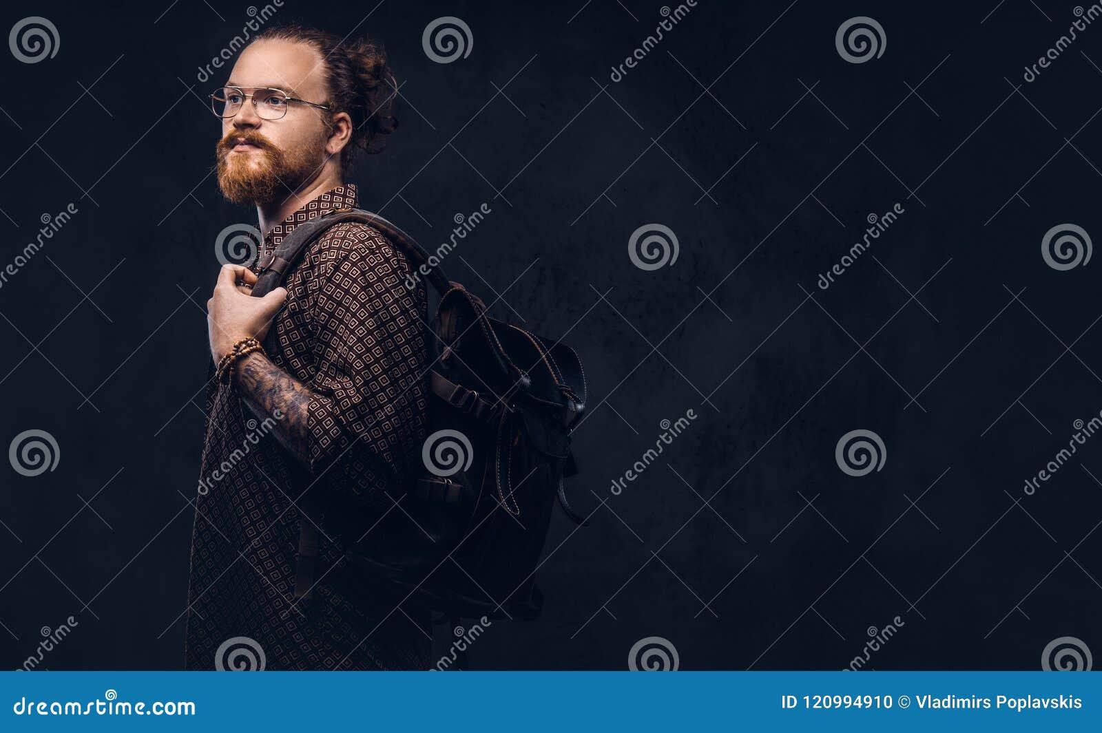 Porträt eines Rothaarigehippie-Studenten in den Gläsern gekleidet in einem Braunhemd, Griffe ein Rucksack, werfend an einem Studi