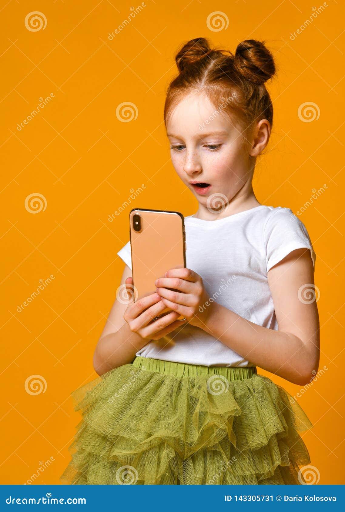 Porträt eines rothaarigen kleinen Mädchens, das intelligentes Telefon, stehend gegen eine gelbe Wand schaut