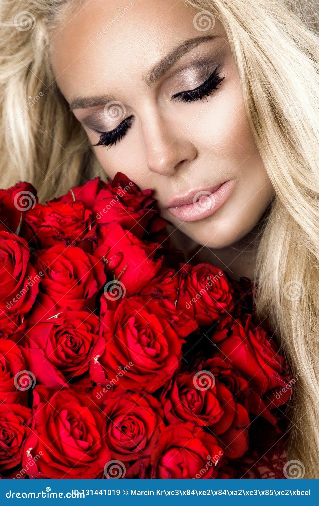 Porträt eines schönen blonden weiblichen Modells mit dem langen, schönen Haar Modell in der sexy Wäsche, rote Rosen halten
