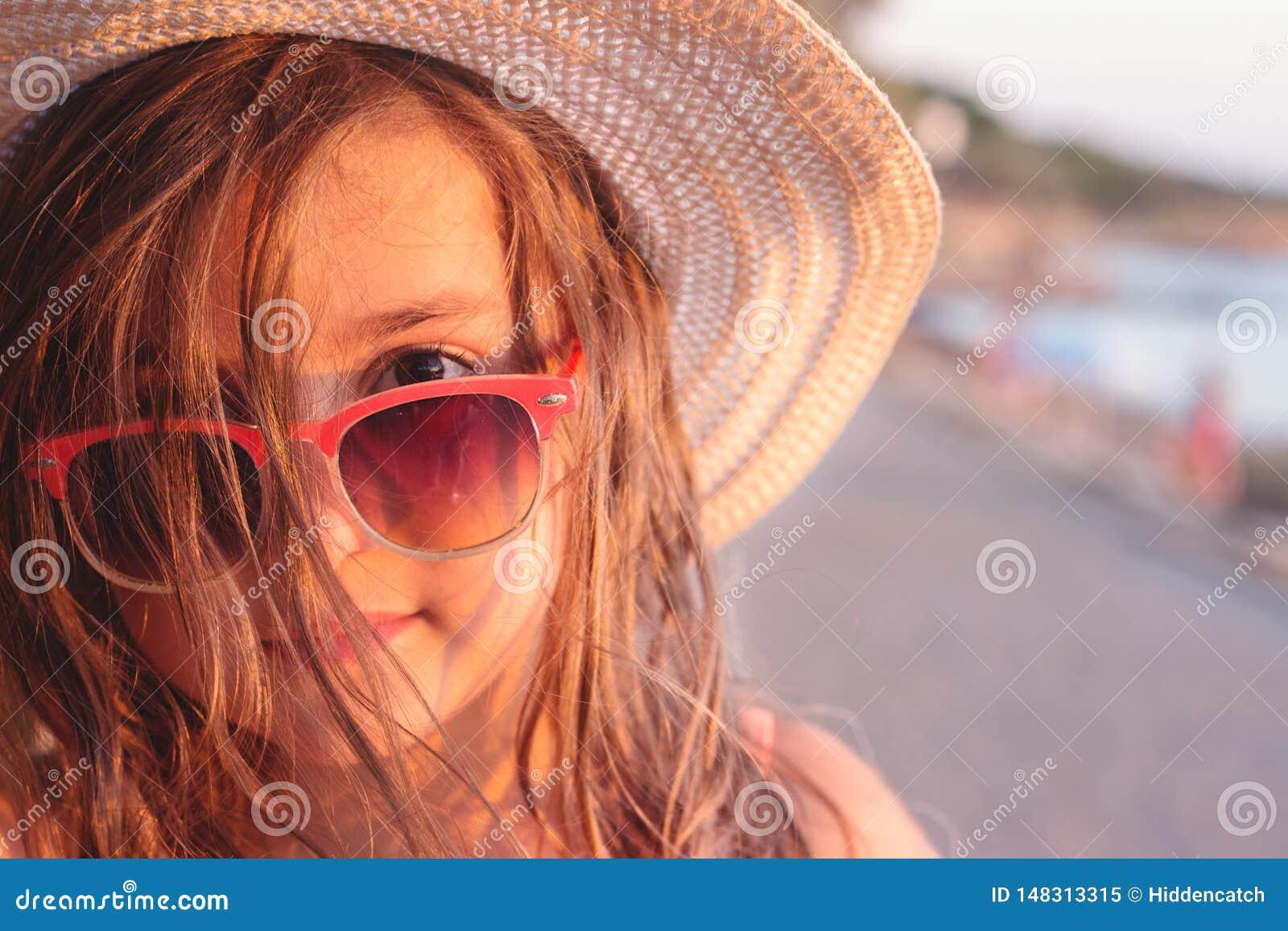 Portr?t eines sch?nen kleinen M?dchens mit Sonnenbrille und Strohhut auf dem Strand