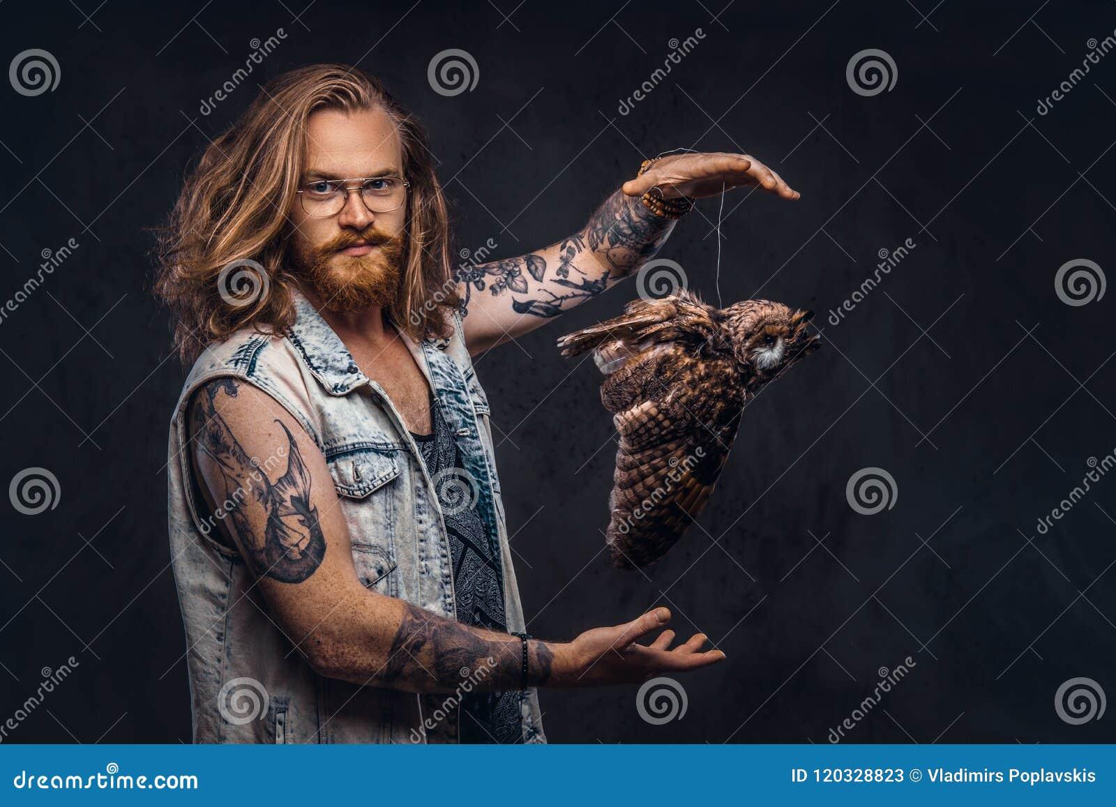 Porträt eines tattoed Rothaarigehippie-Mannes mit dem langen luxuriösen Haar und des Vollbarts gekleidet in ein T-Shirt und Jacke