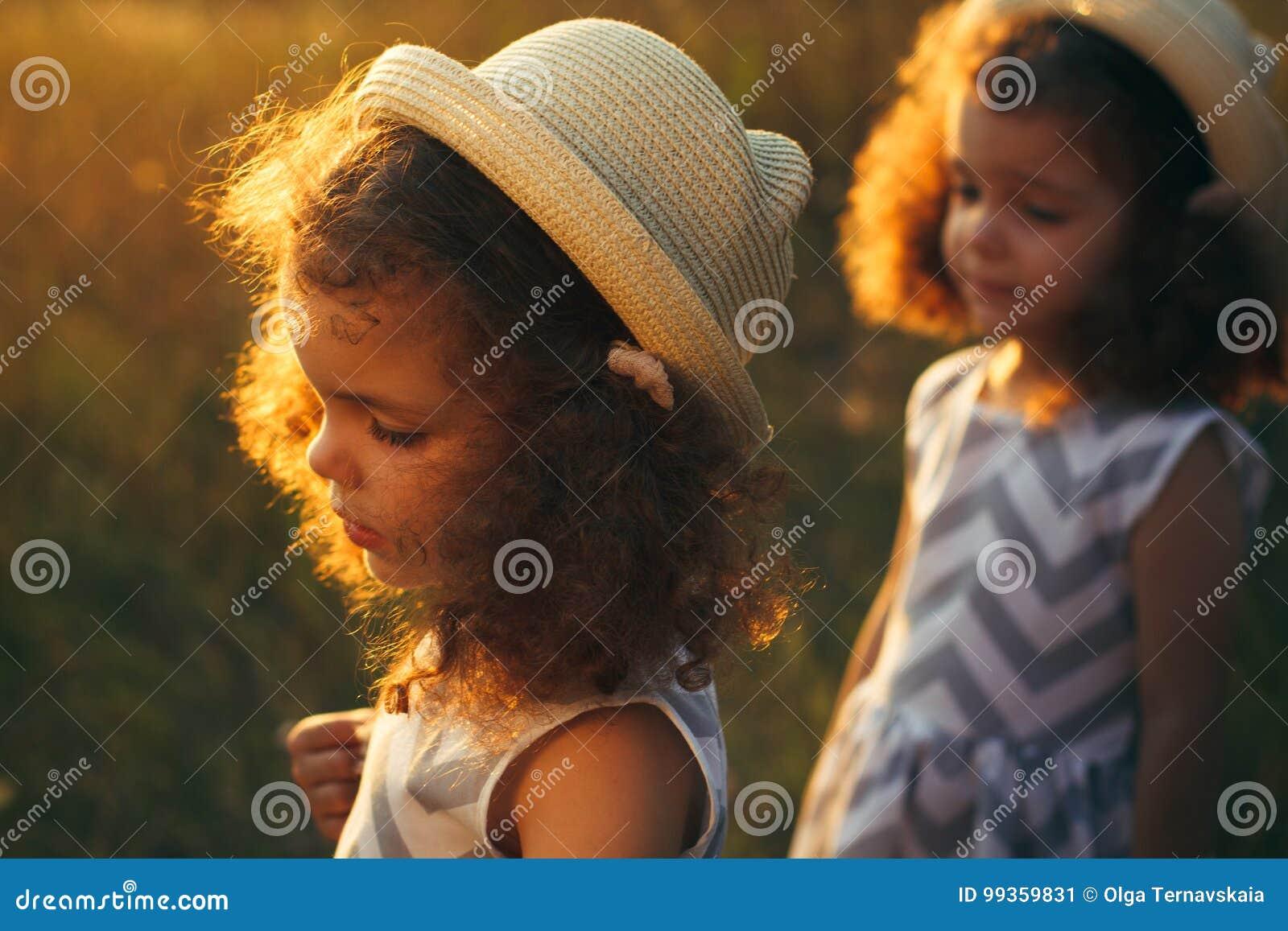 Porträt eines traurigen gelockten kleinen Mädchens und ihrer Zwillingsschwester Schmerzen des kleinen Mädchens Kleinkindmädchen i