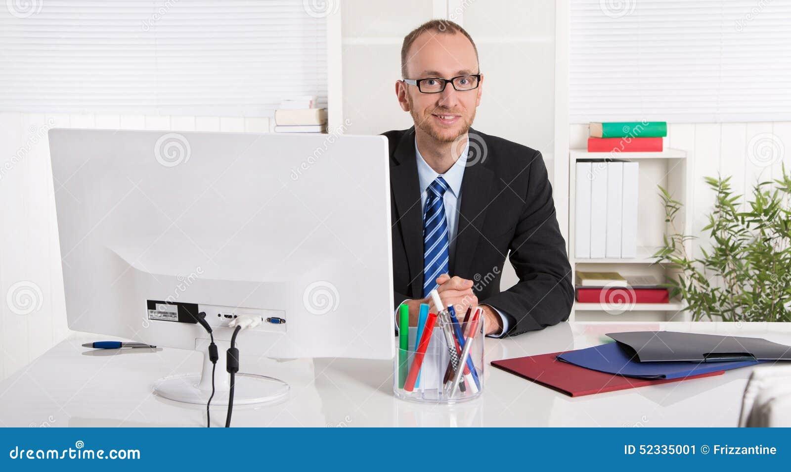 Porträt: Geschäftsmann, der in seinem Büro mit Anzug und Bindung sitzt