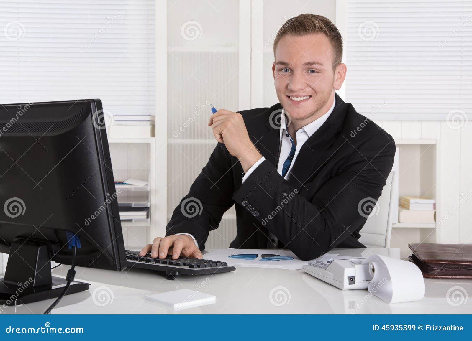 Porträt: Hübscher junger Geschäftsmann in sitzendem herein lächeln der Klage